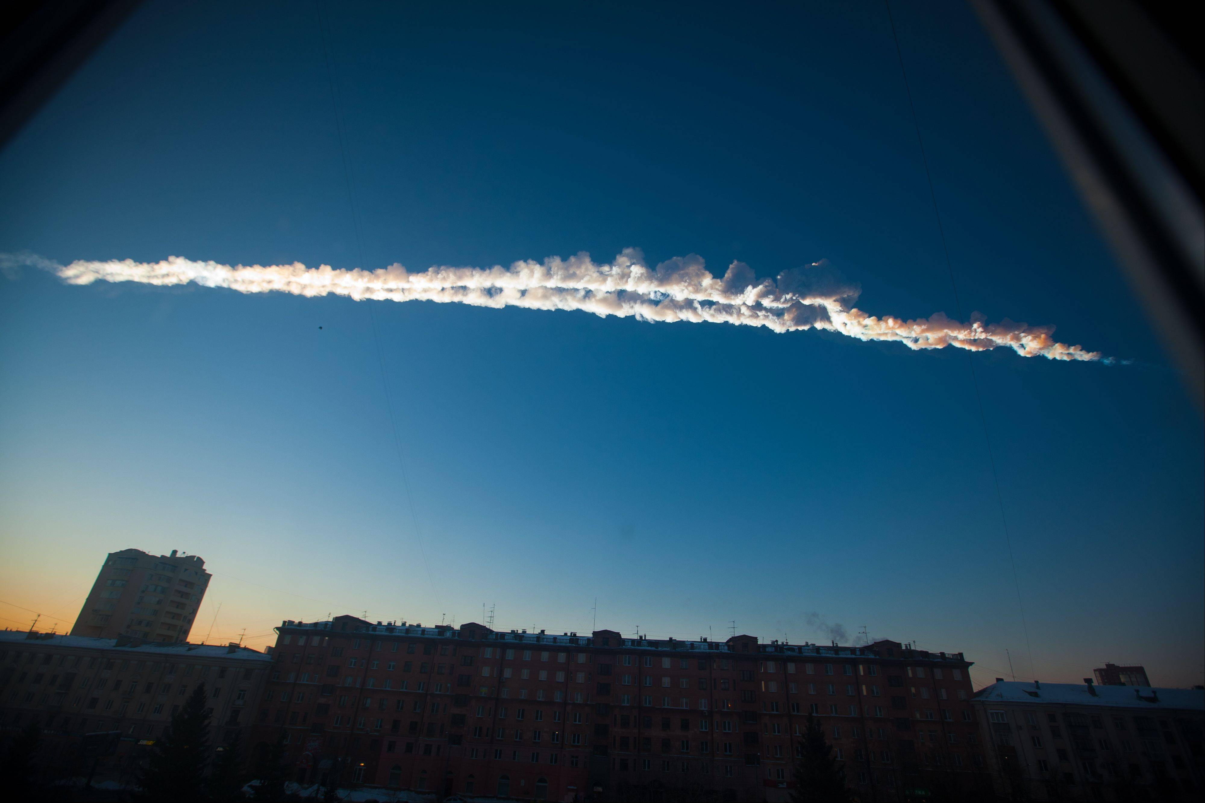 A meteor contrail is seen Friday over Chelyabinsk, Russia. A meteor streaked across the sky of Russia's Ural Mountains on Friday morning, causing sharp explosions and reportedly injuring nearly 1,000 people, including many hurt by broken glass.