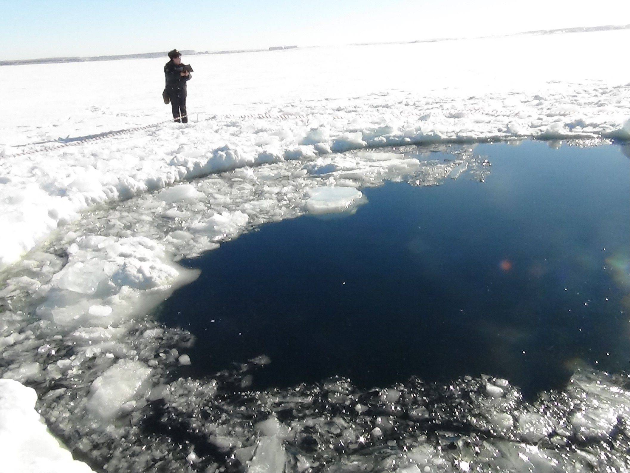 A circular hole in the ice of Chebarkul Lake where a meteor fragment reportedly struck the lake near Chelyabinsk, about 930 miles east of Moscow, Russia, Friday, Feb. 15, 2013. A meteor streaked across the sky and exploded over Russia's Ural Mountains with the power of an atomic bomb Friday, its sonic blasts shattering countless windows and injuring nearly 1,000 people.