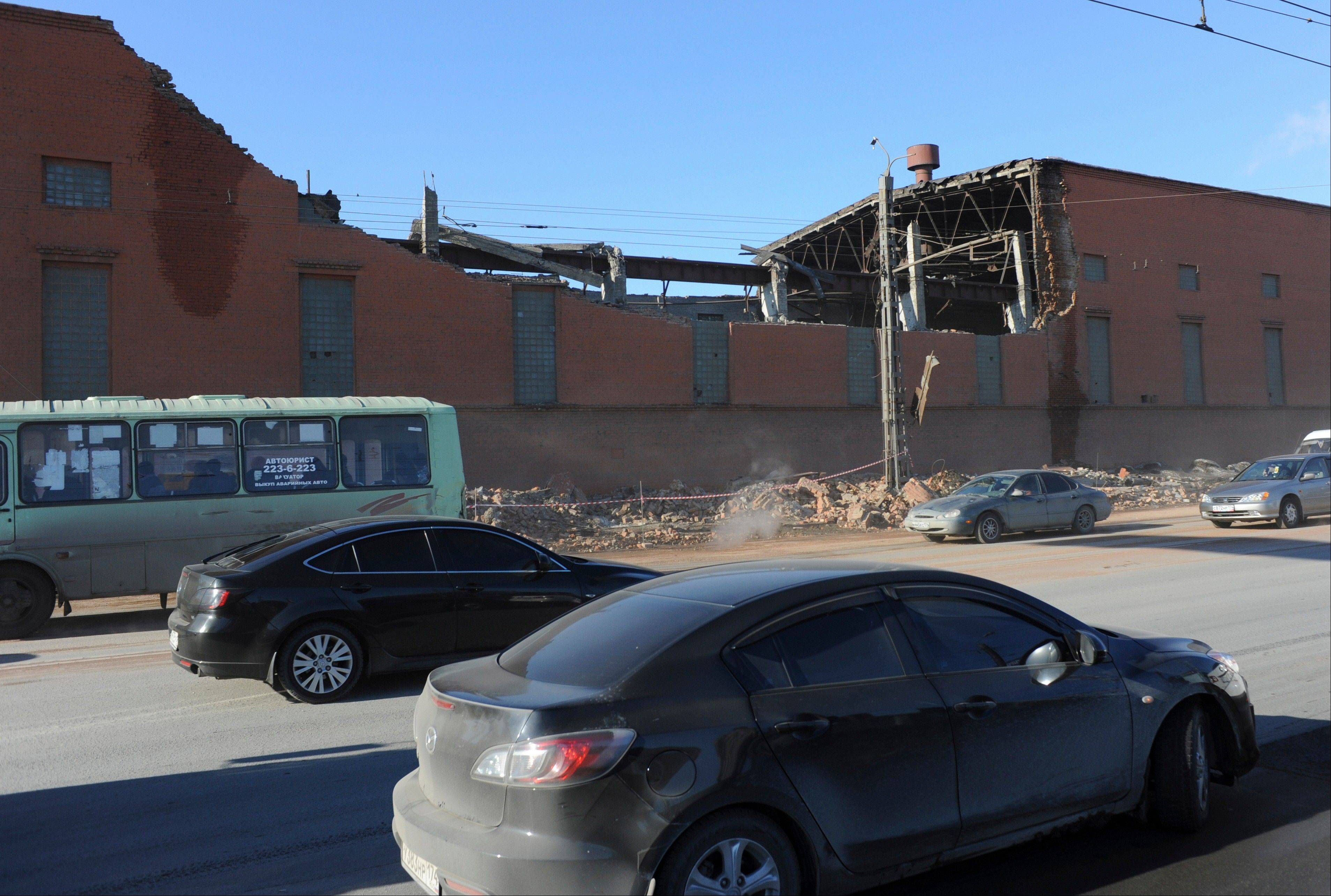 Cars pass by a zinc factory building with it's roof collapsed in Chelyabinsk. There was no immediate clarification of whether the collapse was caused by meteor fragments or by a shock wave from one of the explosions. A meteor that scientists estimate weighed 10 tons streaked at supersonic speed over Russia's Ural Mountains on Friday, setting off blasts that injured some 500 people and frightened countless more.