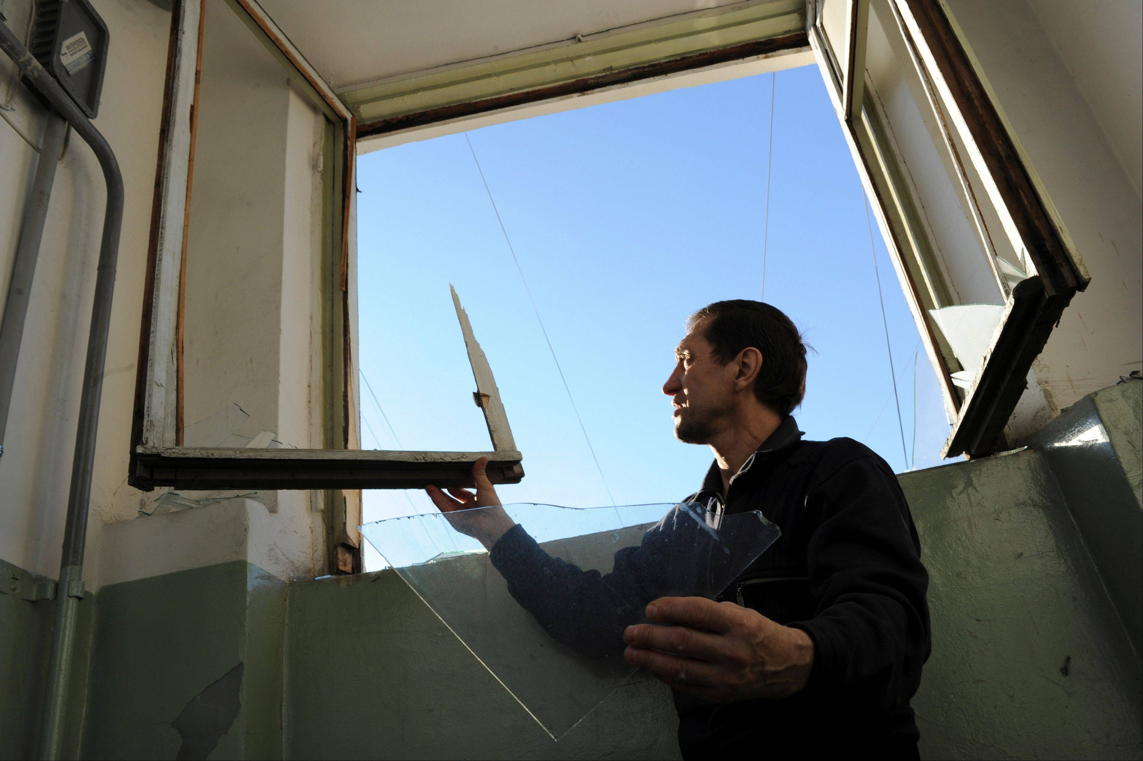 A local resident repairs a window broken by a shock wave from a meteor explosion in Chelyabinsk, about 930 miles east of Moscow, Friday, Feb. 15, 2013.