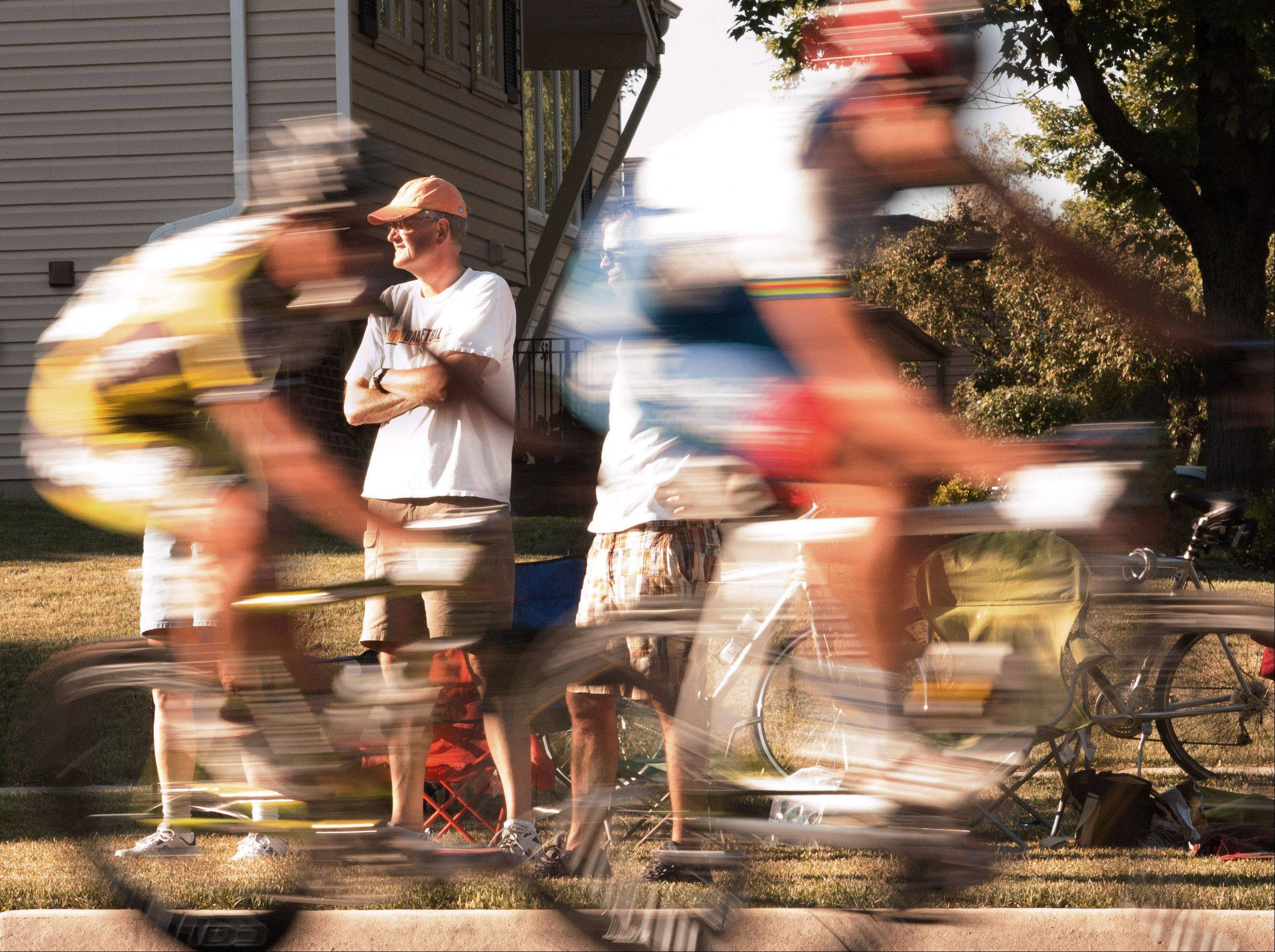 A spectator watches as pro cyclists fly by during the Tour of Elk Grove at the corner of Weathersfield Way and Cedarcrest Drive in Schaumburg in 2008. Riders reached speeds close to 30 miles an hour.