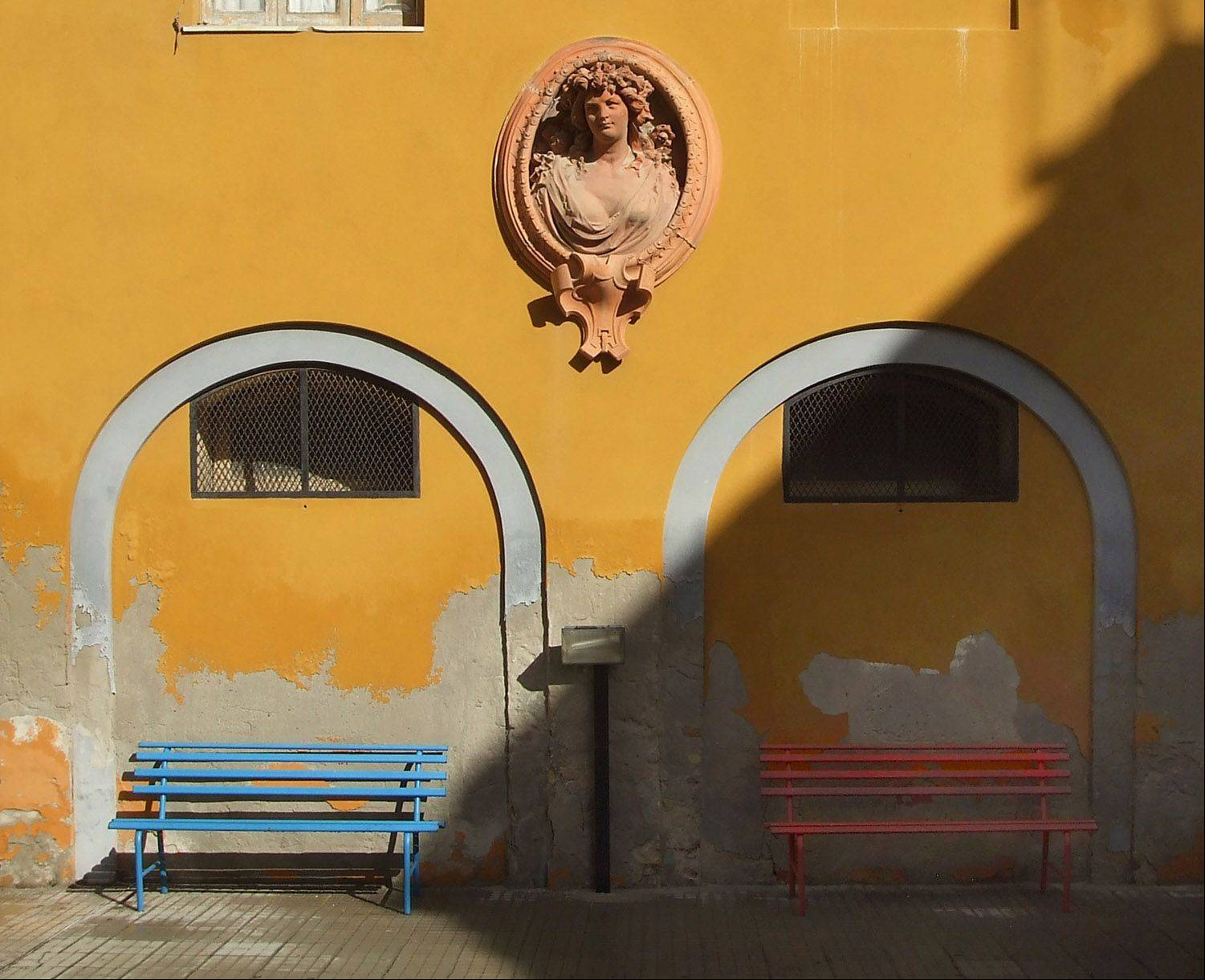 A beautiful terra cotta sculpture of a woman guards a brightly painted courtyard in Cagliari, Sardinia off the western coast of Italy on a recent cruise.