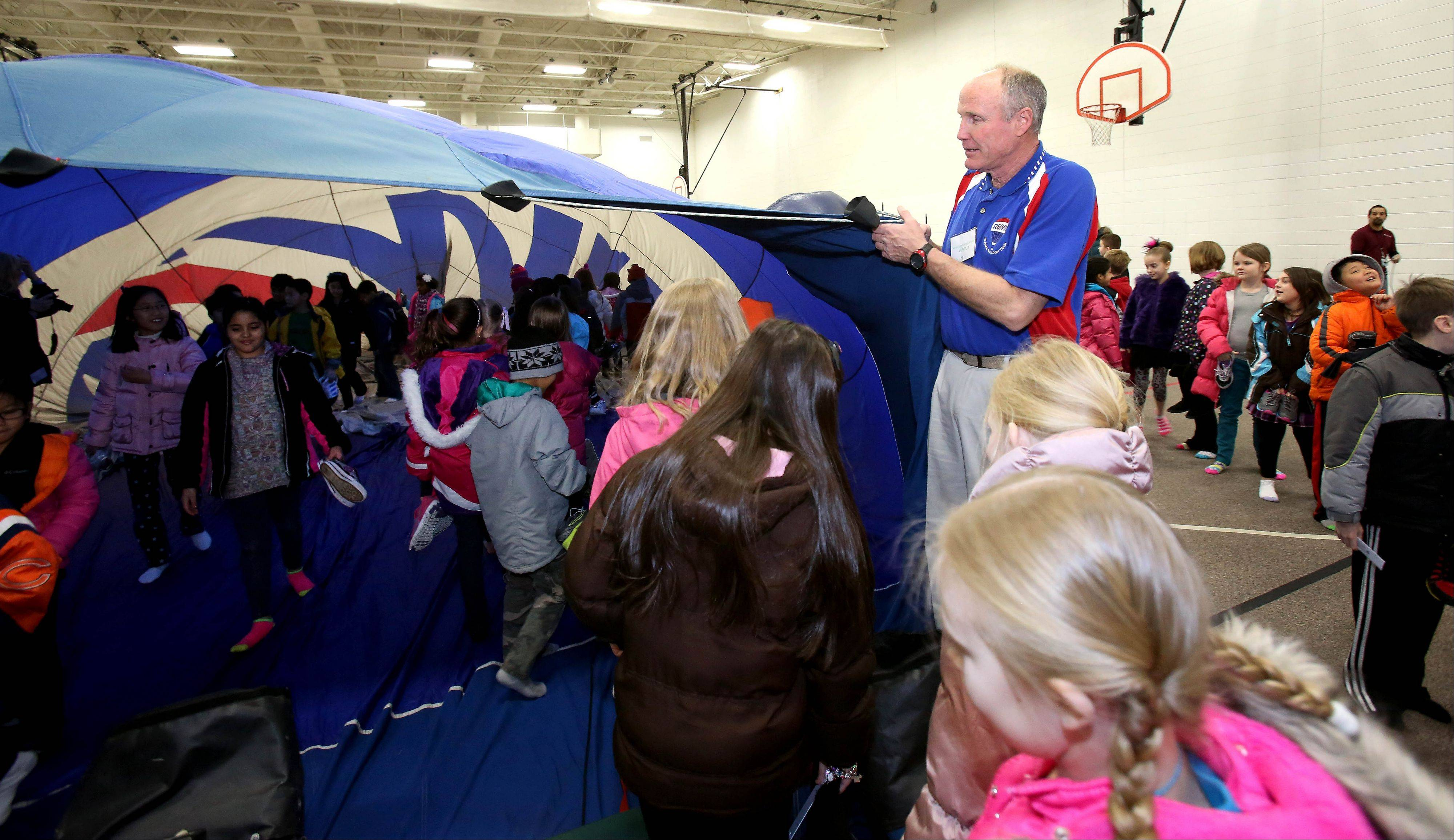 Bill Baker, a hot-air balloon pilot with RE/MAX, holds the partially inflated balloon so kids from Welch Elementary School in Naperville can walk around inside.