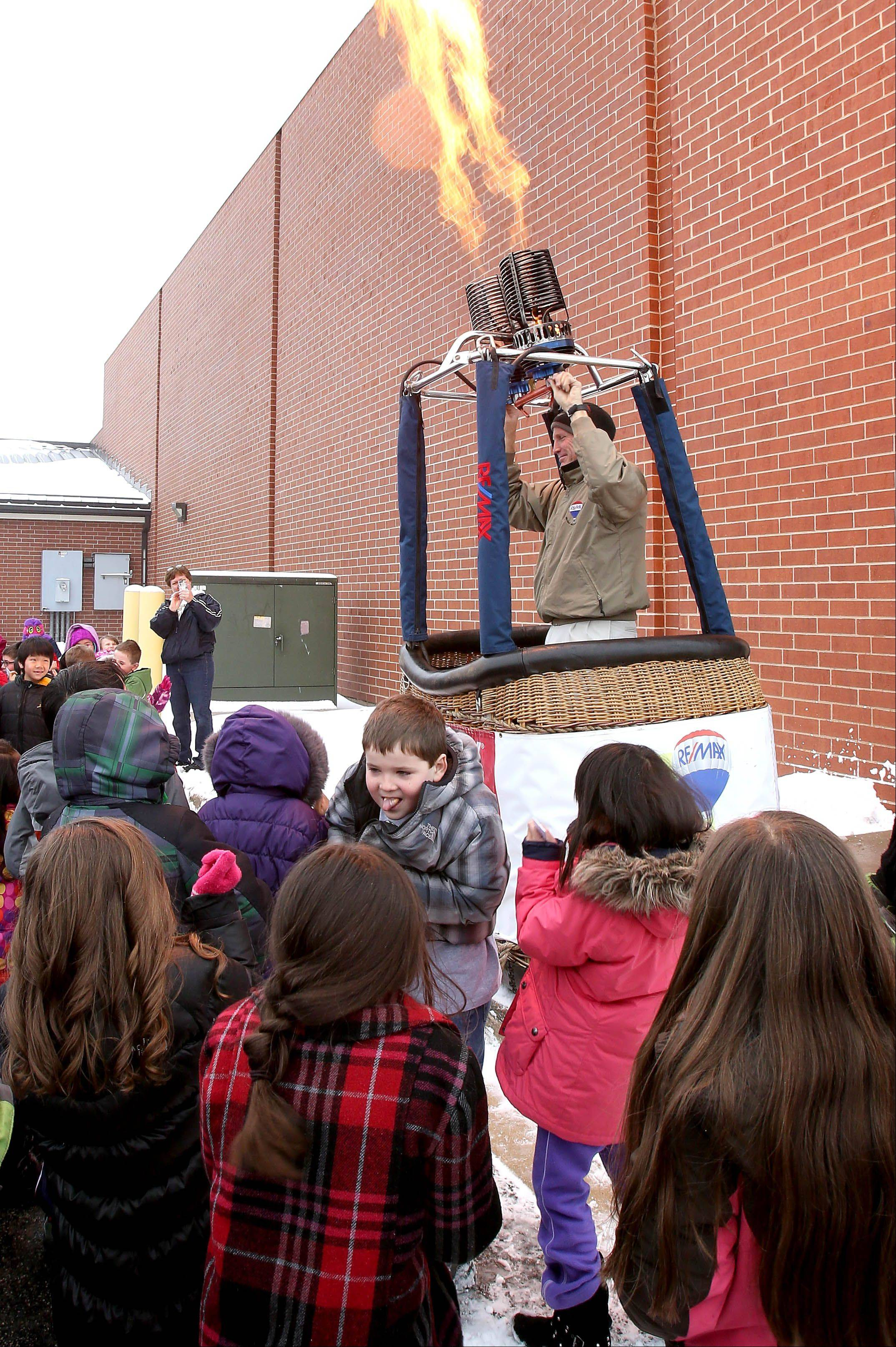 Bill Baker, a hot-air balloon pilot with RE/MAX, sets off the burners for kids at Welch Elementary School in Naperville.