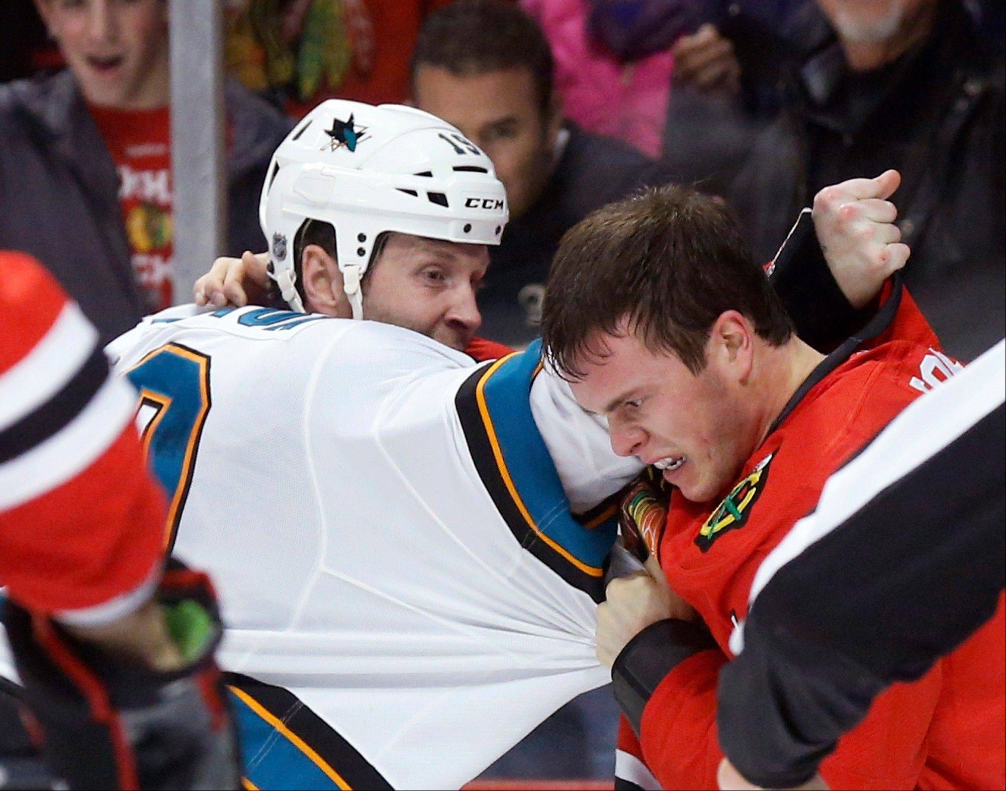 Blackhawks captain Jonathan Toews mixes it up with Sharks captain Joe Thornton in the first period Friday night at the United Center.