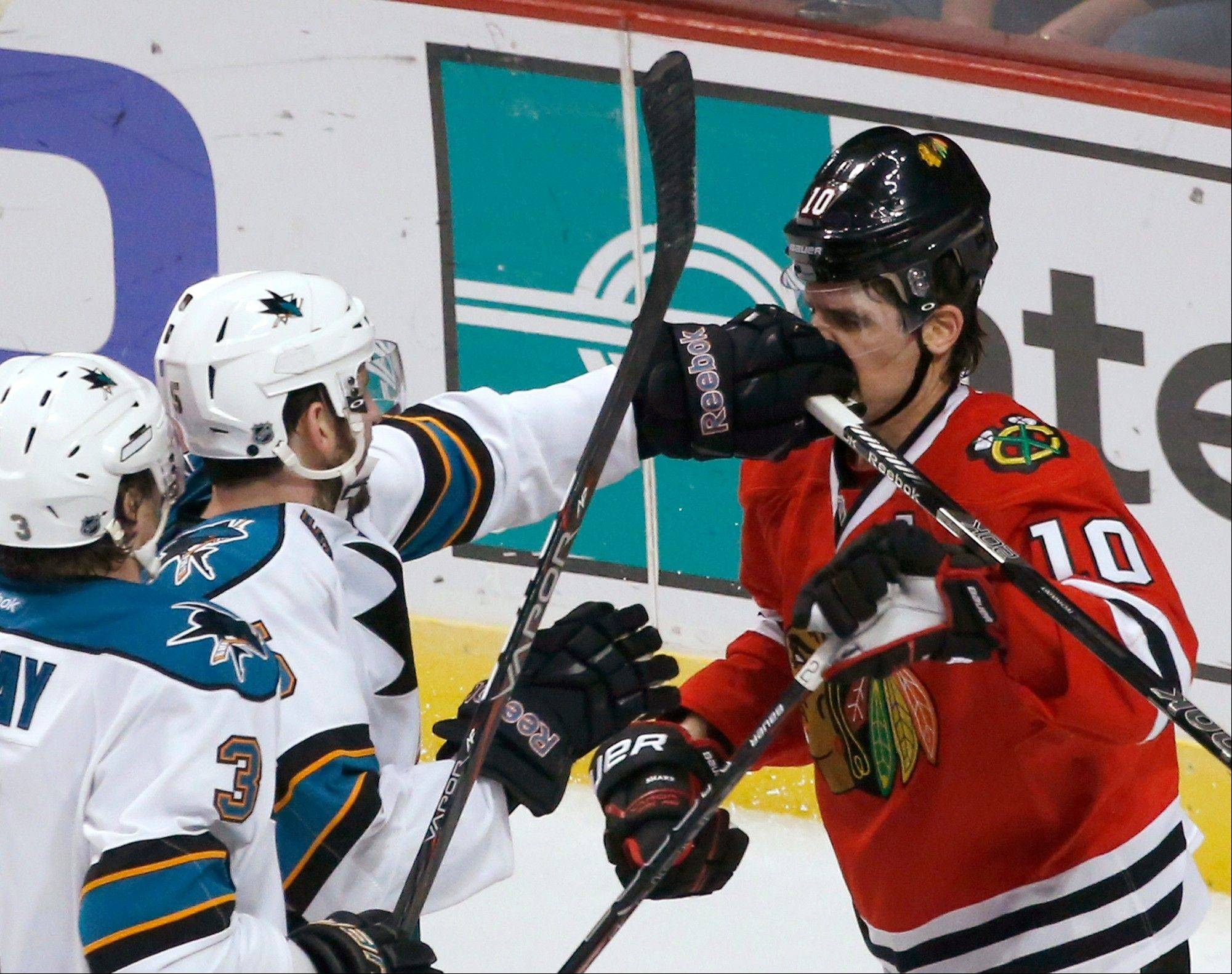 San Jose Sharks defenseman Jason Demers (5) take a jab at Chicago Blackhawks center Patrick Sharp (10) as Douglas Murray (3) watches during the second period of an NHL hockey game Friday, Feb. 15, 2013, in Chicago.
