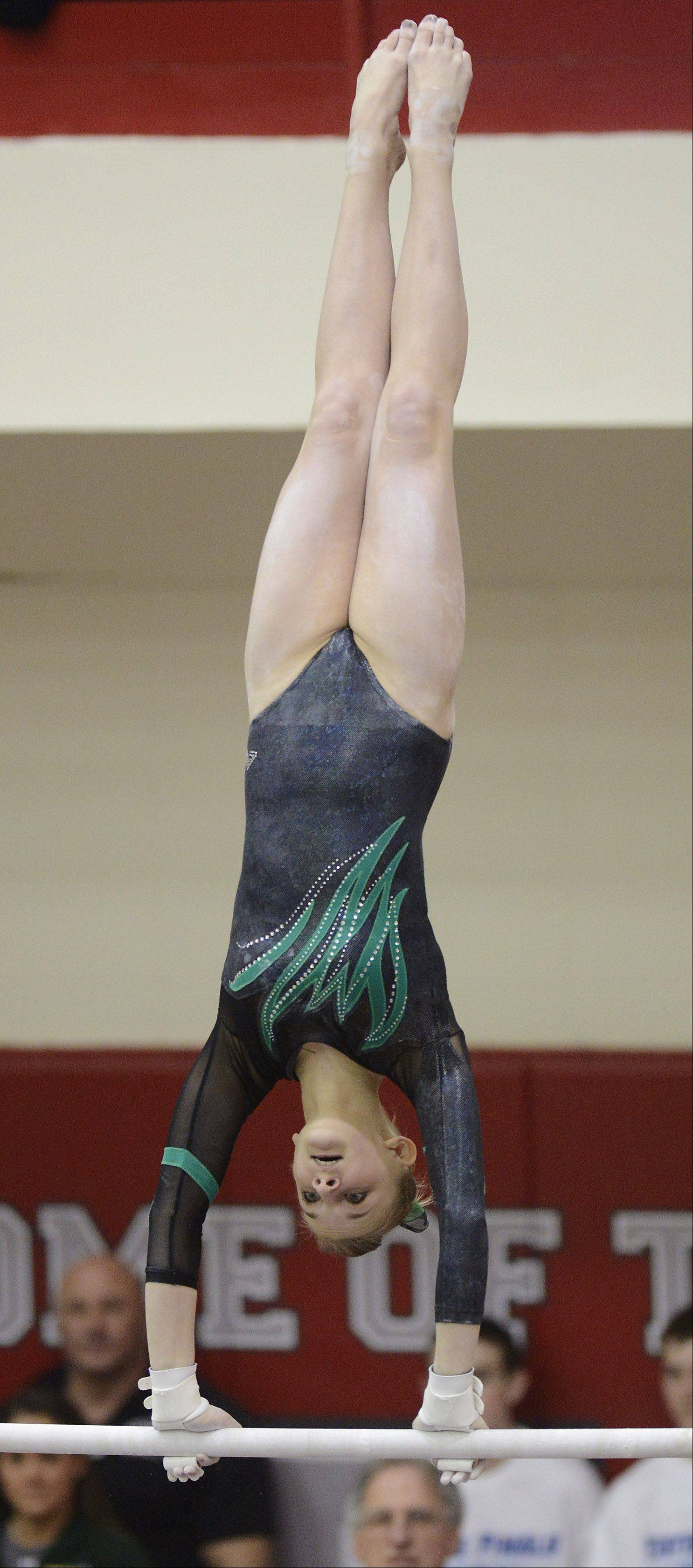 Fremd's Sydney Plichta competes on the uneven parallel bars during the girls gymnastics state preliminaries at Palatine High School on Friday.
