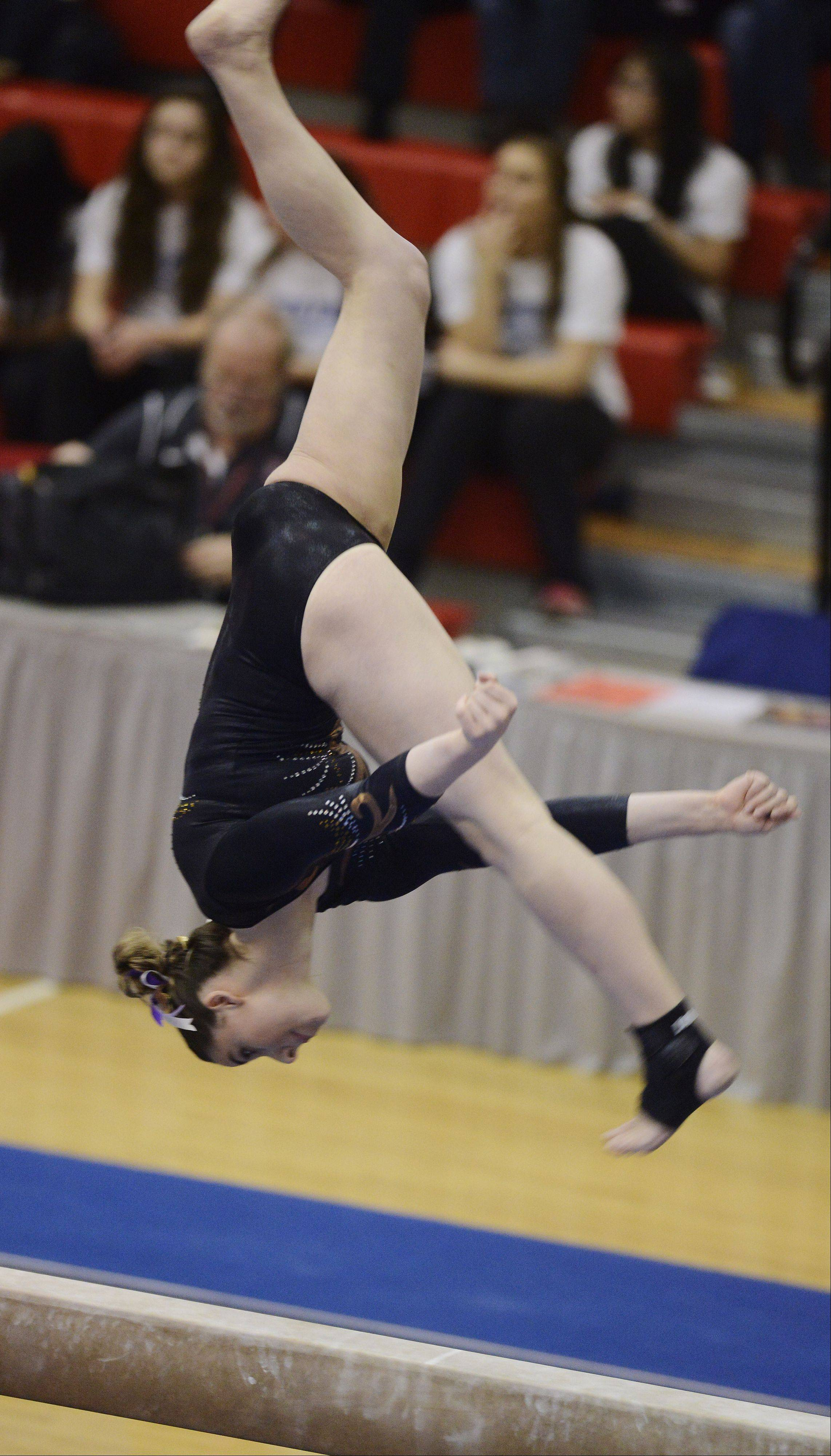 Carmel's Lauren Feely competes on the balance beam during the girls gymnastics state preliminaries at Palatine High School on Friday.