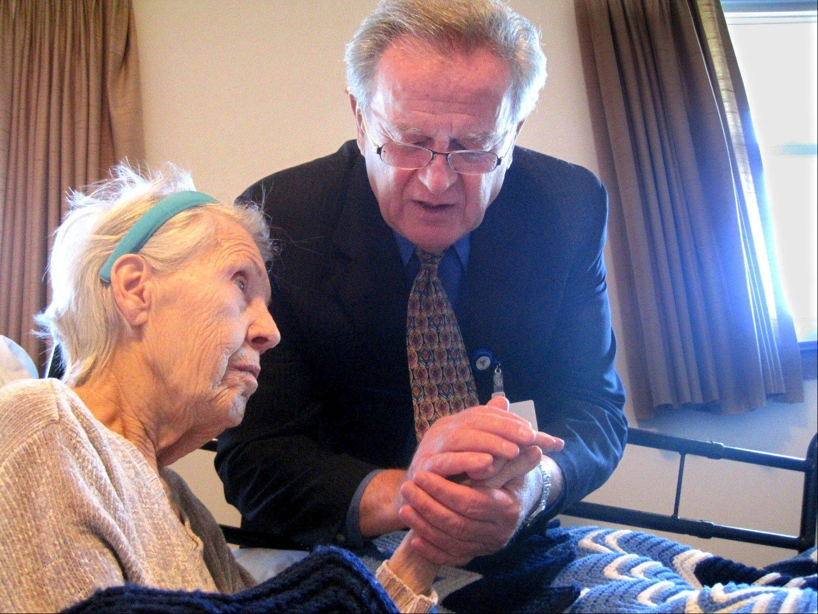 Chaplain Branislav Dedic of Bartlett counsels Helen Bukovsky at her home in Westchester.