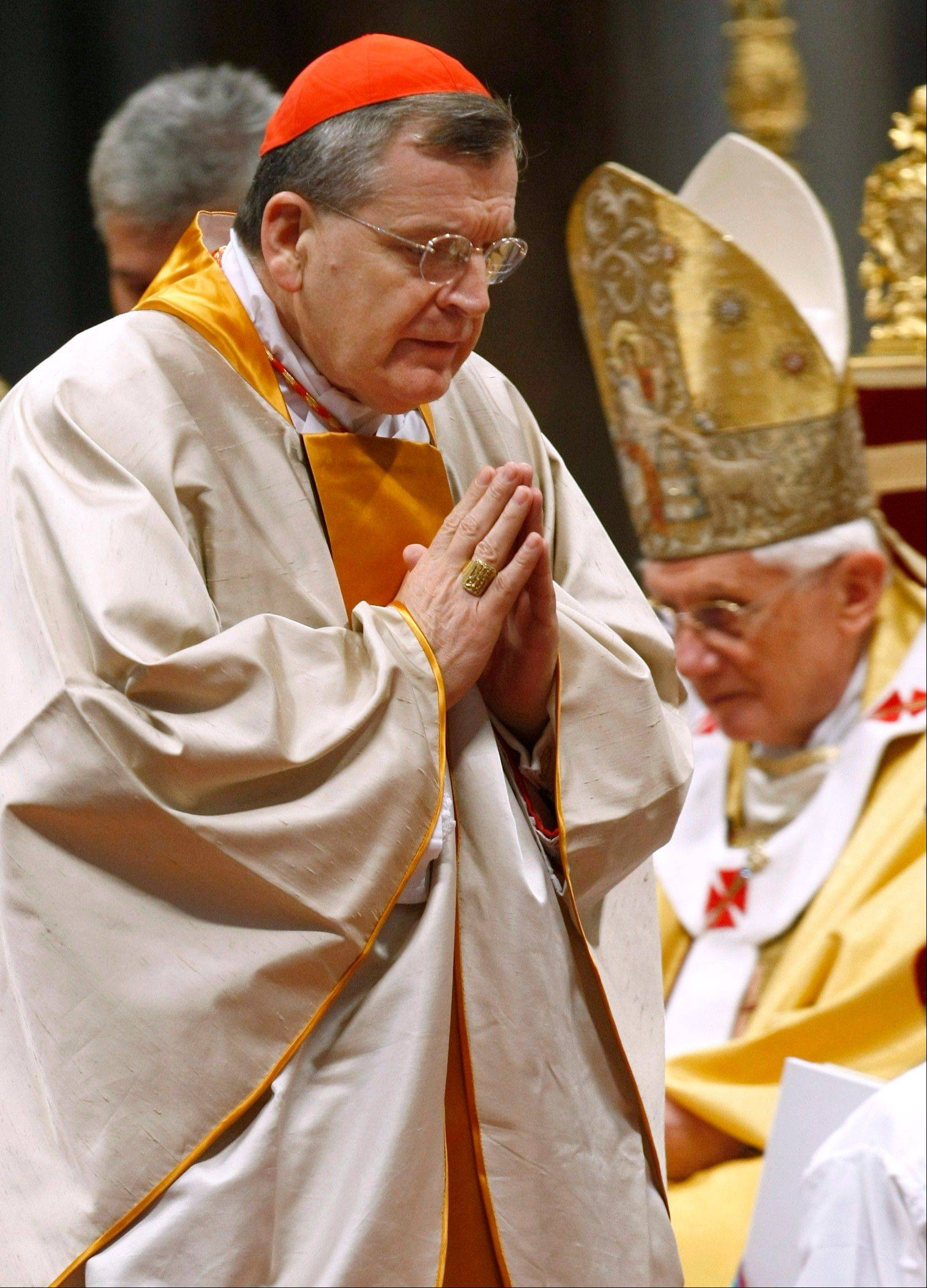 Newly appointed U.S. Cardinal Raymond Leo Burke walks past Pope Benedict XVI after receiving Cardinal�s ring during a mass in St. Peter�s Basilica, at the Vatican. Burke, the former St. Louis archbishop, is the first American to lead the Vatican supreme court.
