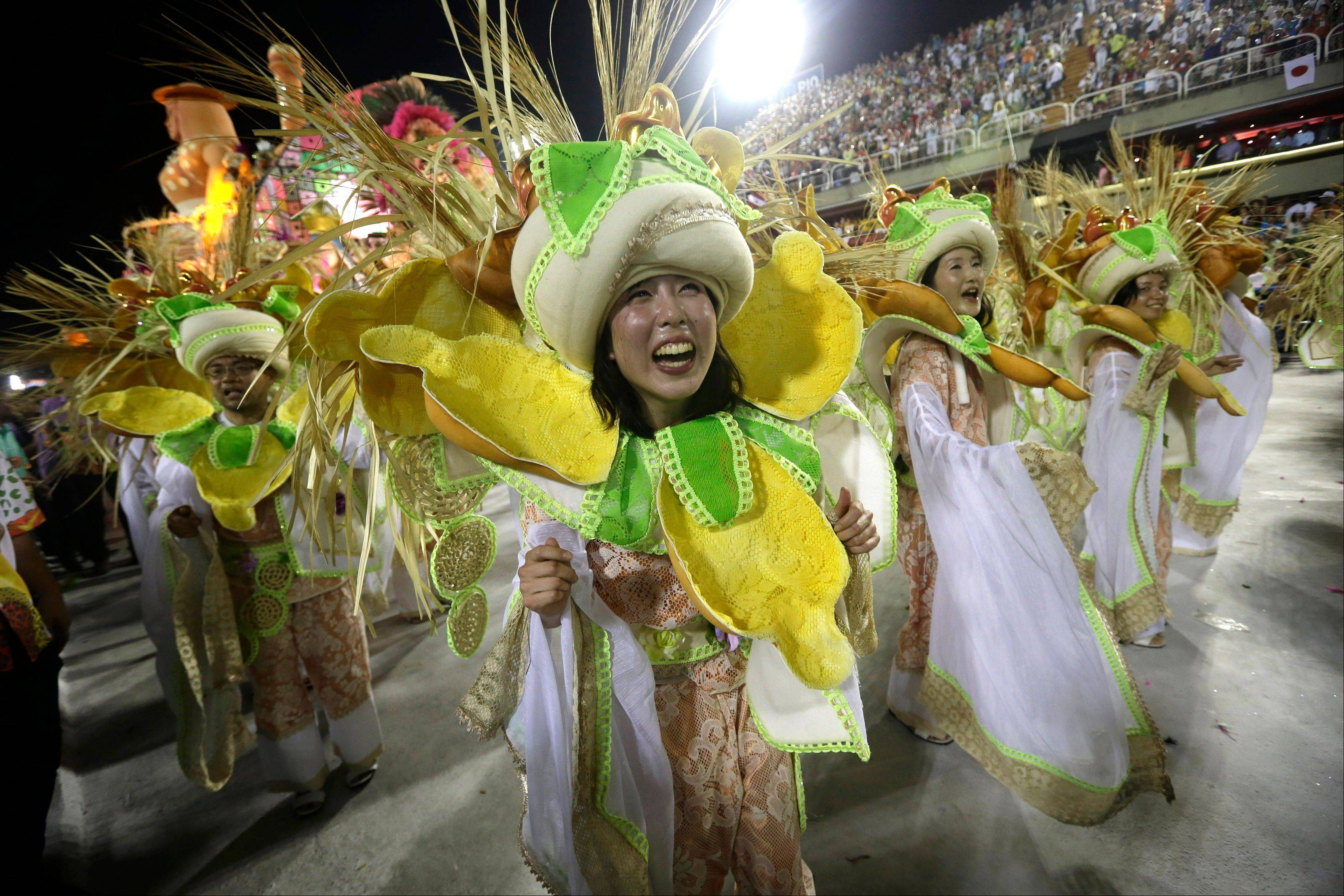 "Japanese performers from the Mangueira samba school parade during carnival celebrations at the Sambadrome in Rio de Janeiro, Brazil, Tuesday. While non-Brazilians have long shelled out hundreds of dollars for the right to dress up in over-the-top costumes and boogie in Rio's samba school parades, few in the so-called ""alas dos gringos,"" or ""foreigners' wings,"" know how to dance the samba well, bopping along goofily in the parades and waving at the crowds of spectators."