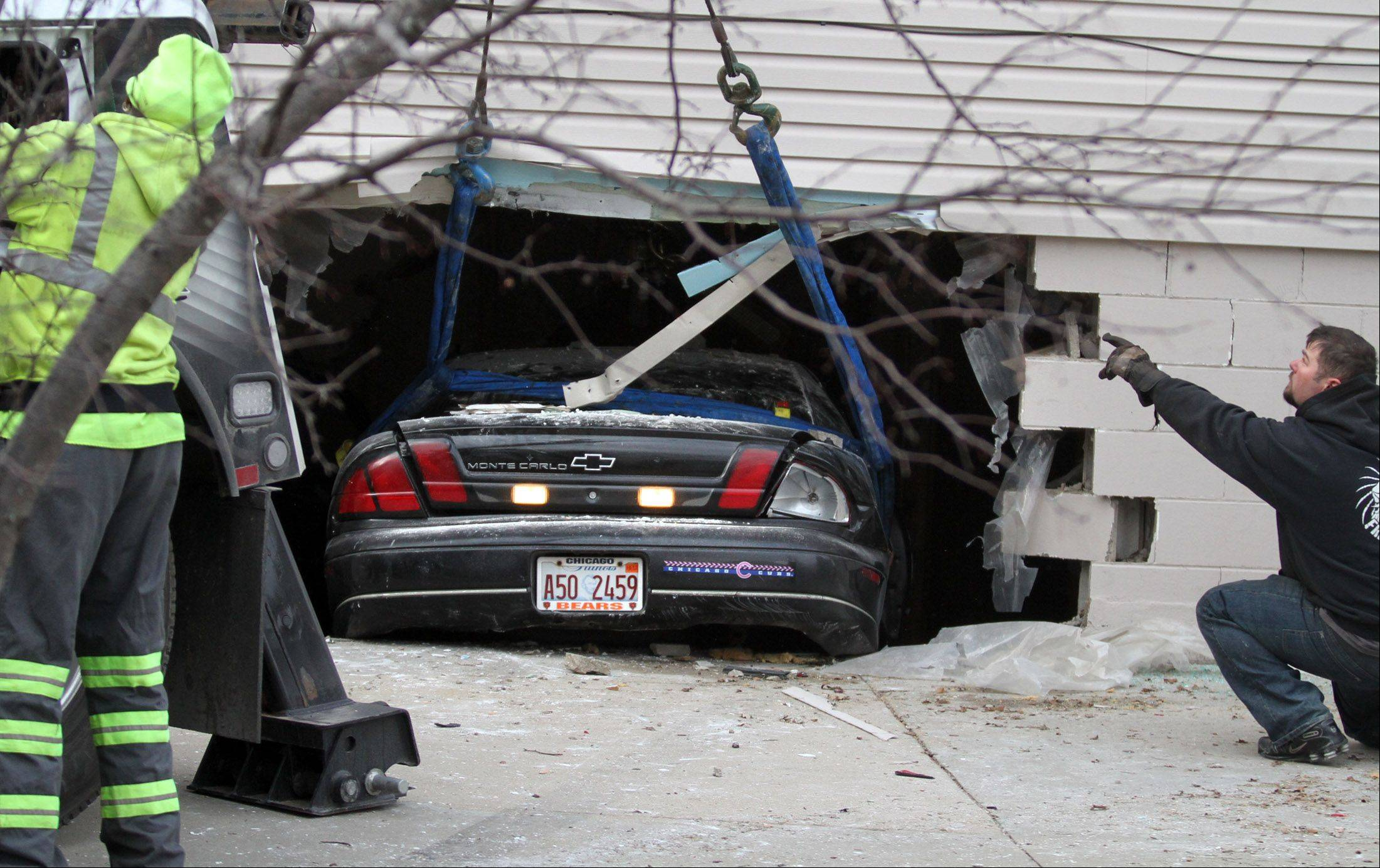 Streamwood firefighters and tow truck operators had to be careful not to further damage the structural integrity of the home in the 900 block of Meadow Lane as they removed the car from the basement.