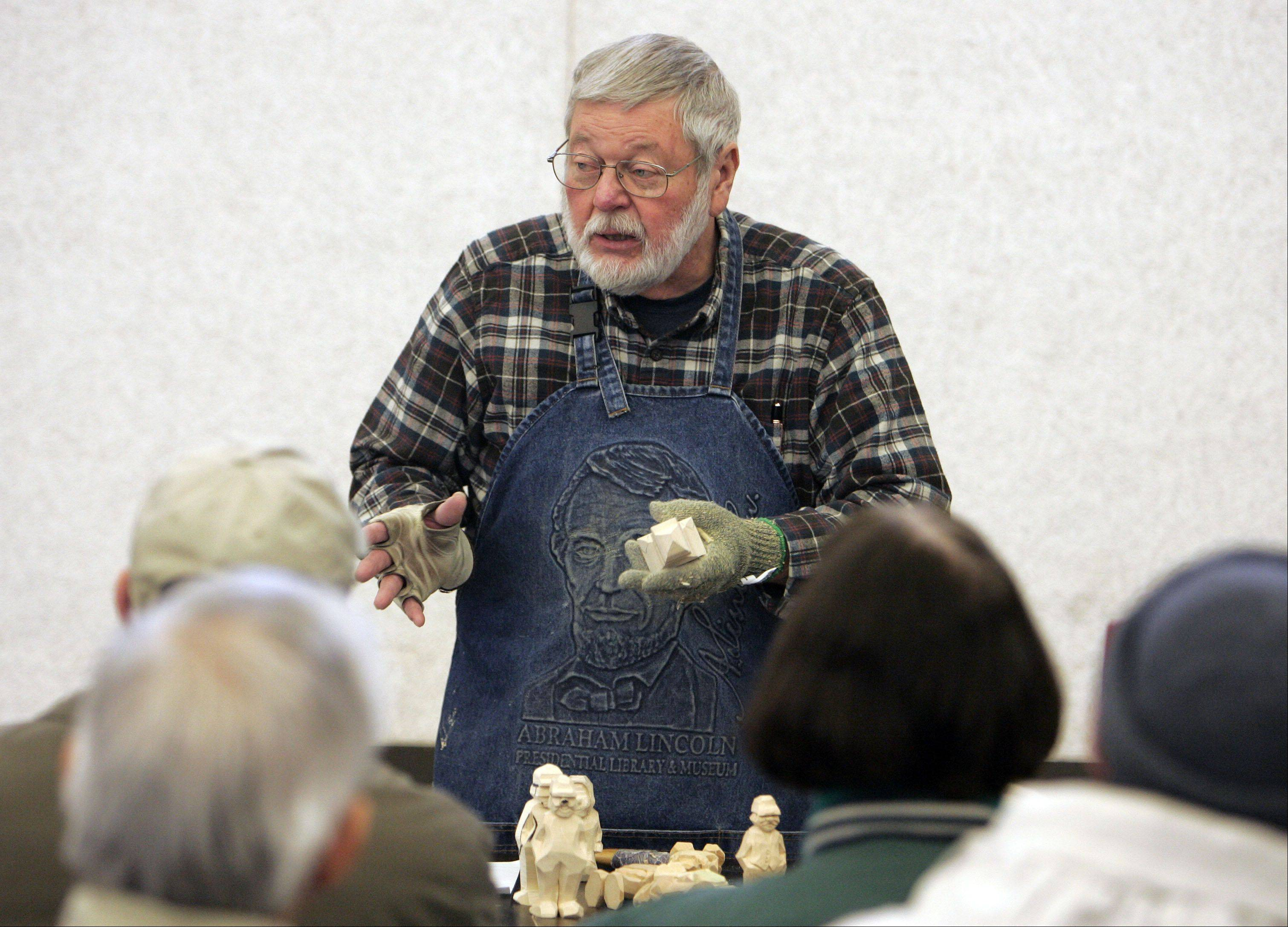 Dave Kublank explains the ins and outs of Scandinavian flat plain carving during a demonstration at the Winter Wood Wonders art show Saturday at the Kane County Fairgrounds in St. Charles.
