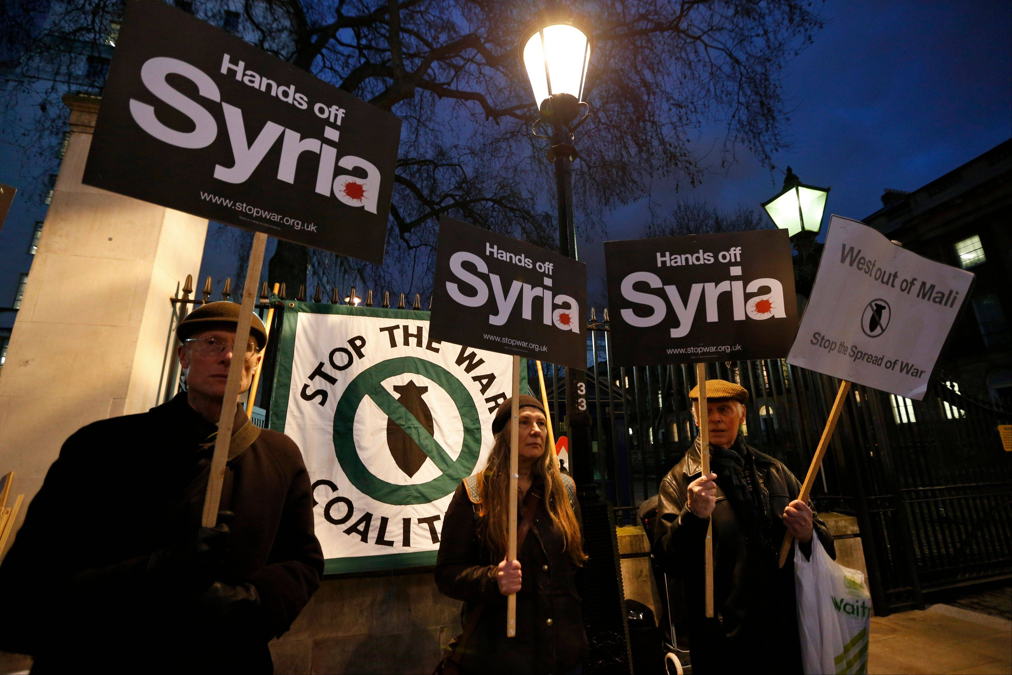 Anti-war protesters from the Stop the War Coalition hold placards Friday night during a rally against western intervention in Syria and calling for western troops to leave Mali, on the 10th anniversary of the march to stop the war in Iraq, opposite the official residence of the British prime minister, in central London.