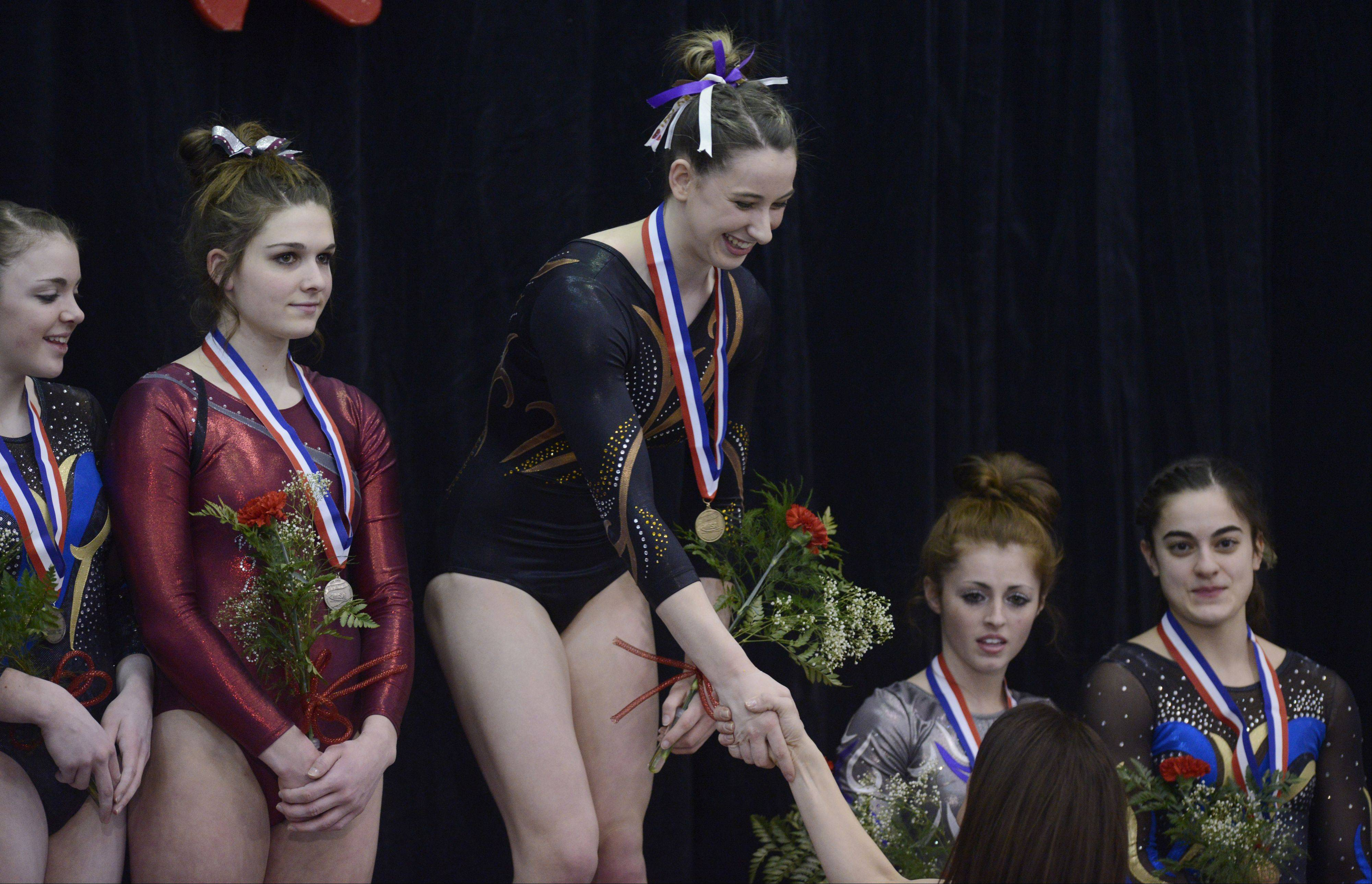 Lauren Feely is congratulated for her medal for the all-around competition during the girls state gymnastics finals at Palatine High School Saturday.