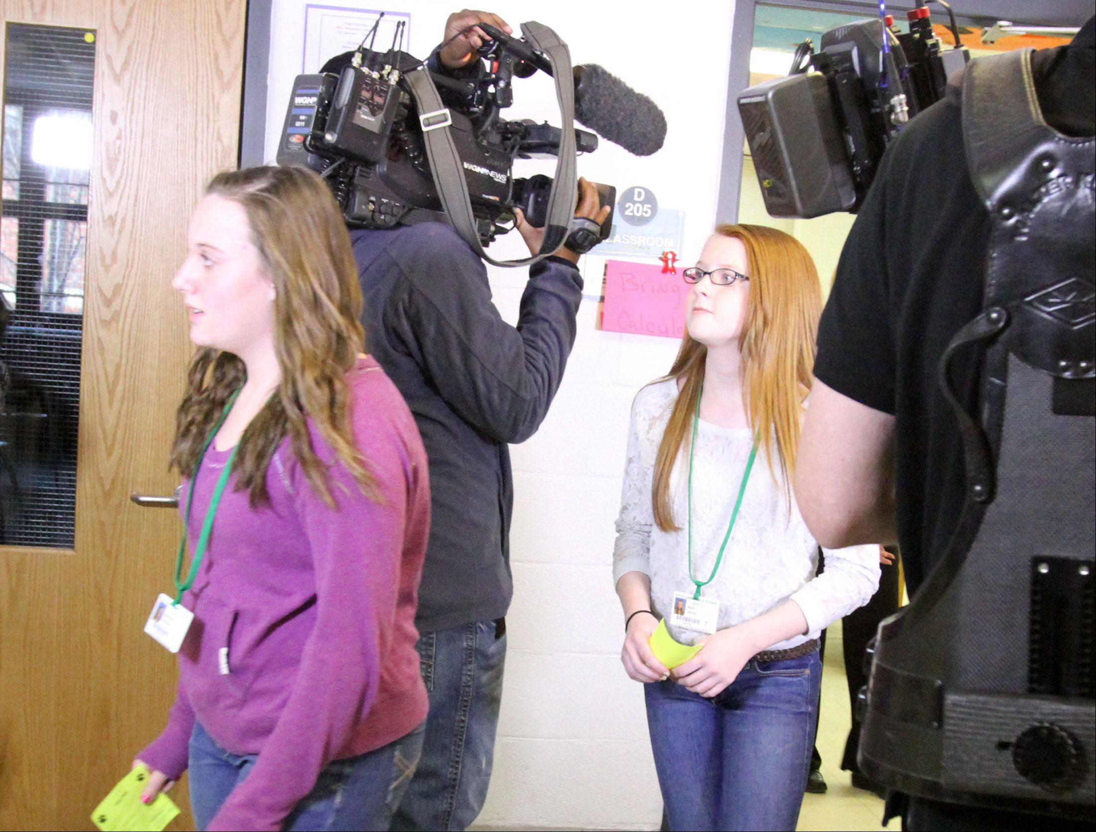 Morgan Niesen, left, and Riley Doyle, both seventh-graders at Woodland Middle School, play their roles of rushing to a hard-lockdown area in a safety video shot Friday at the school in Gurnee.