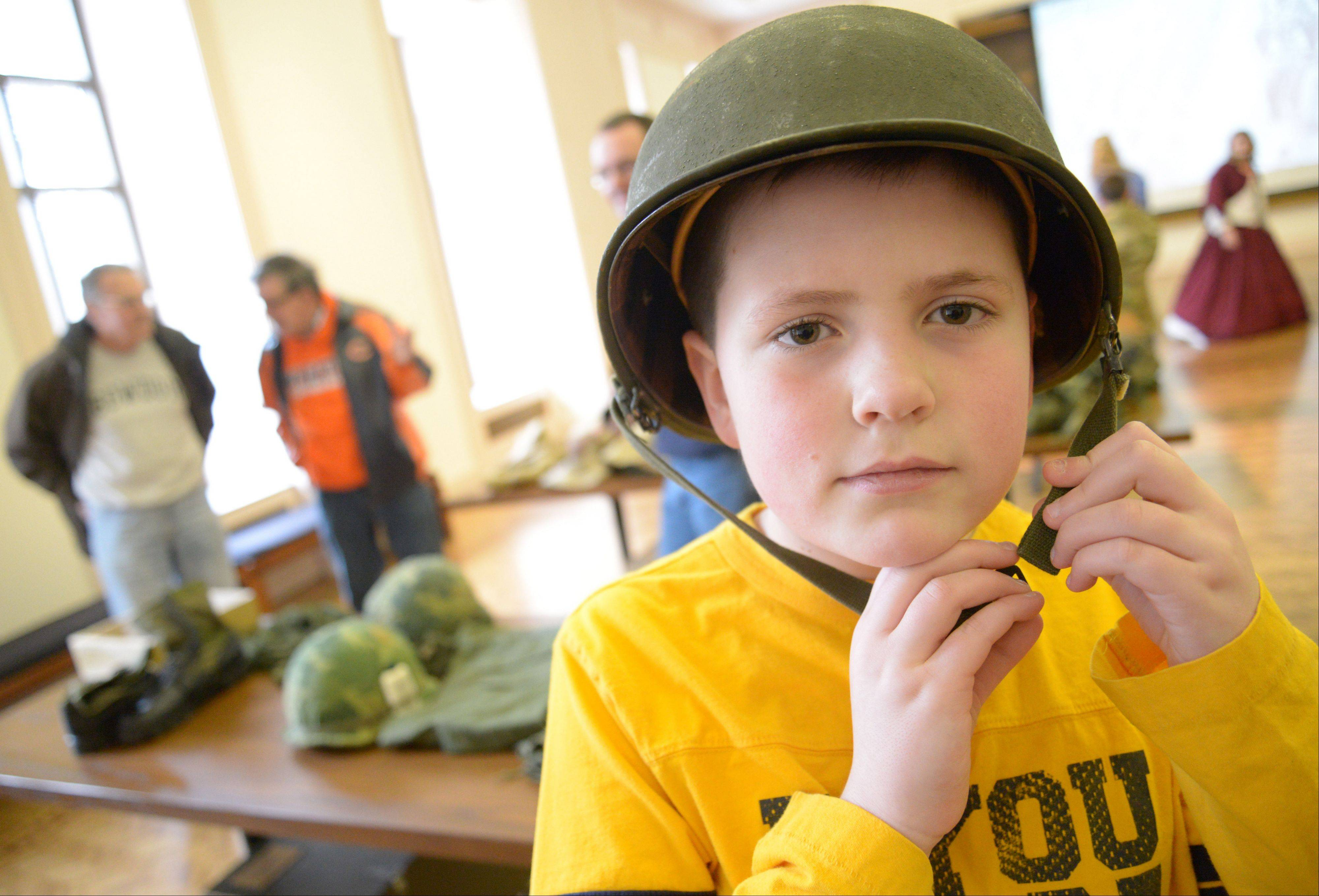 Sean Burke, 9, of Chicago, tries on a World War II-era helmet during the open house Saturday at the First Division Museum at Cantigny Park in Wheaton.