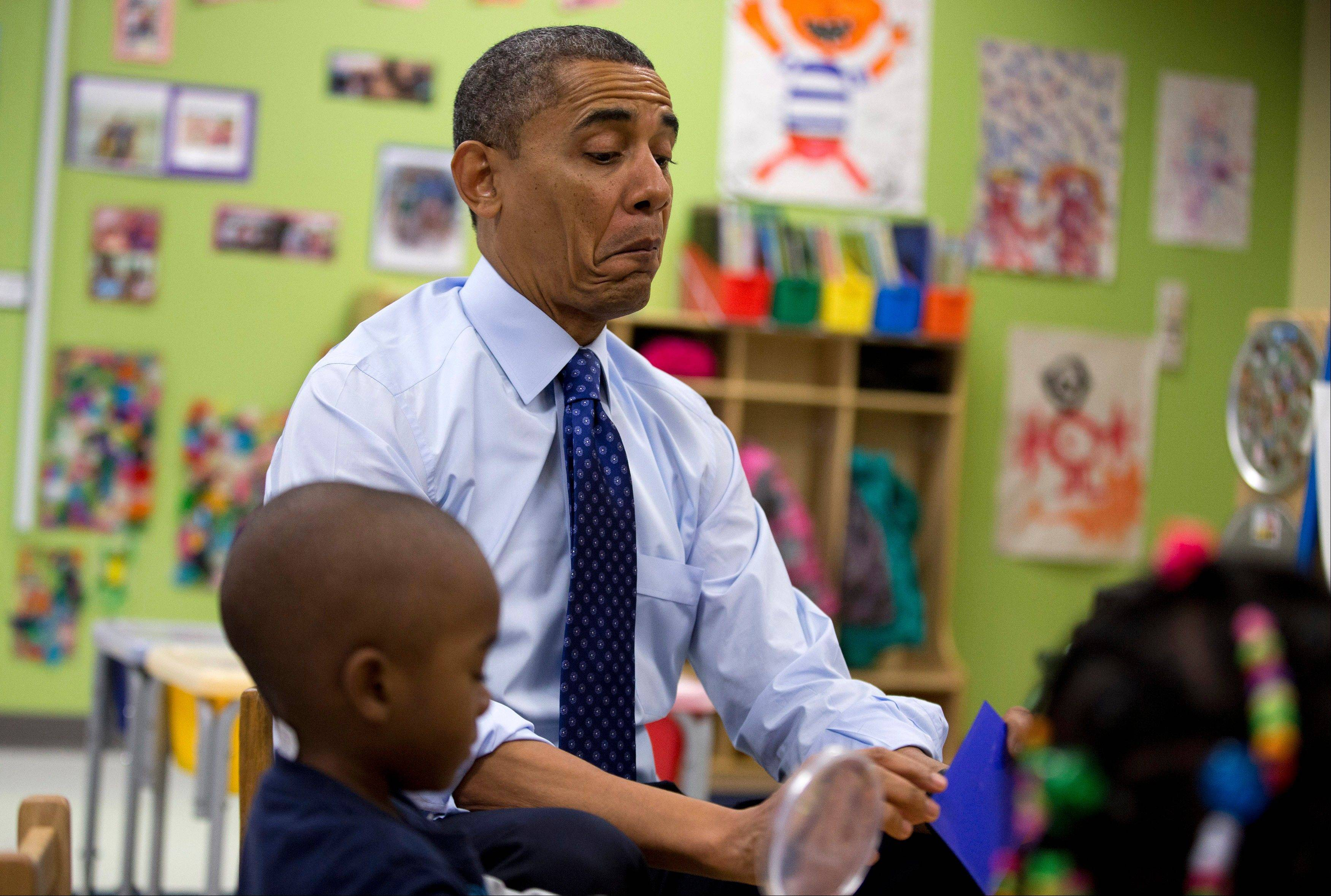 President Barack Obama reacts as he draws a card Thursday during a learning game during a visit to a pre-kindergarten classroom at College Heights Early Childhood Learning Center in Decatur, Ga.