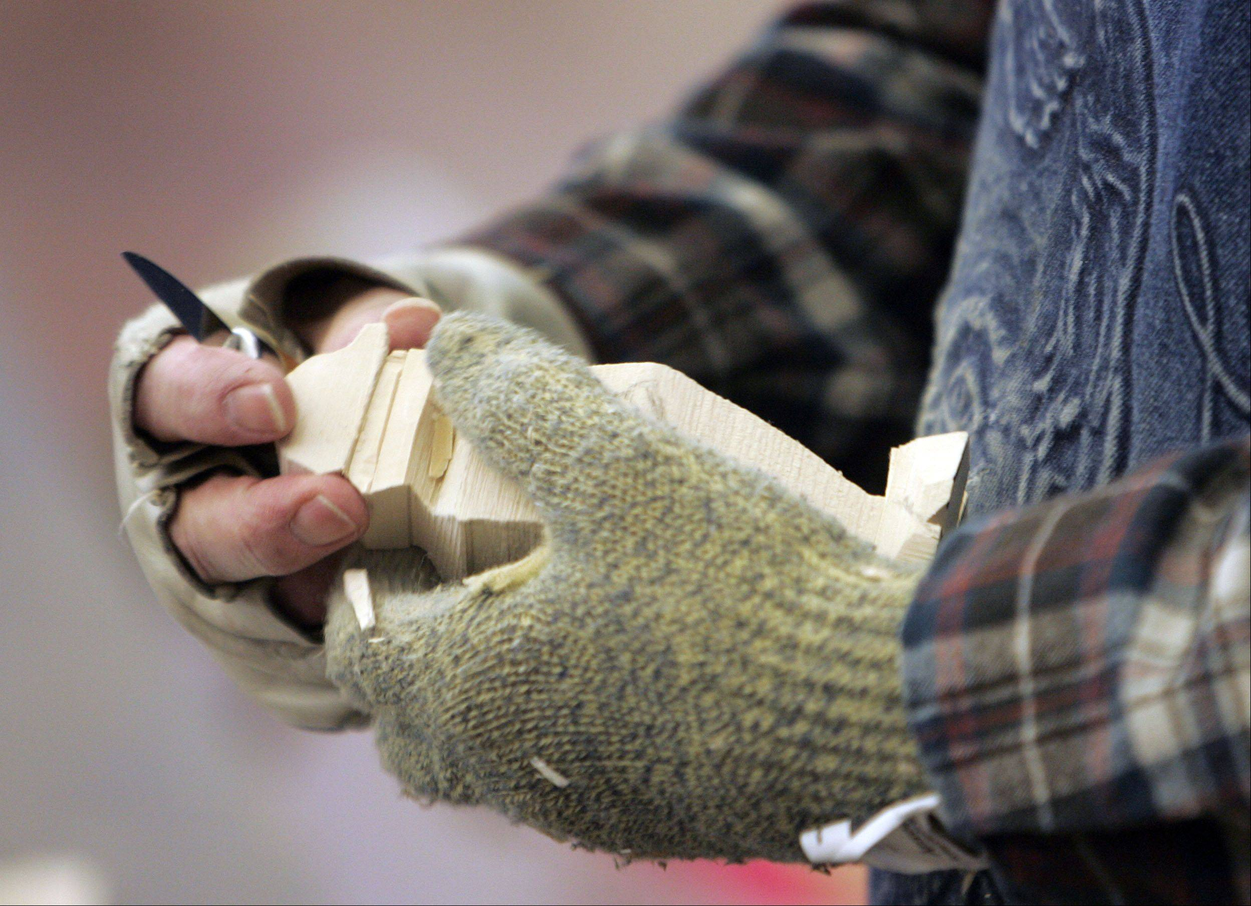 Dave Kublank explains how to do Scandinavian flat plain carving during a demonstration at the Winter Wood Wonders art show Saturday at the Kane County Fairgrounds in St. Charles.