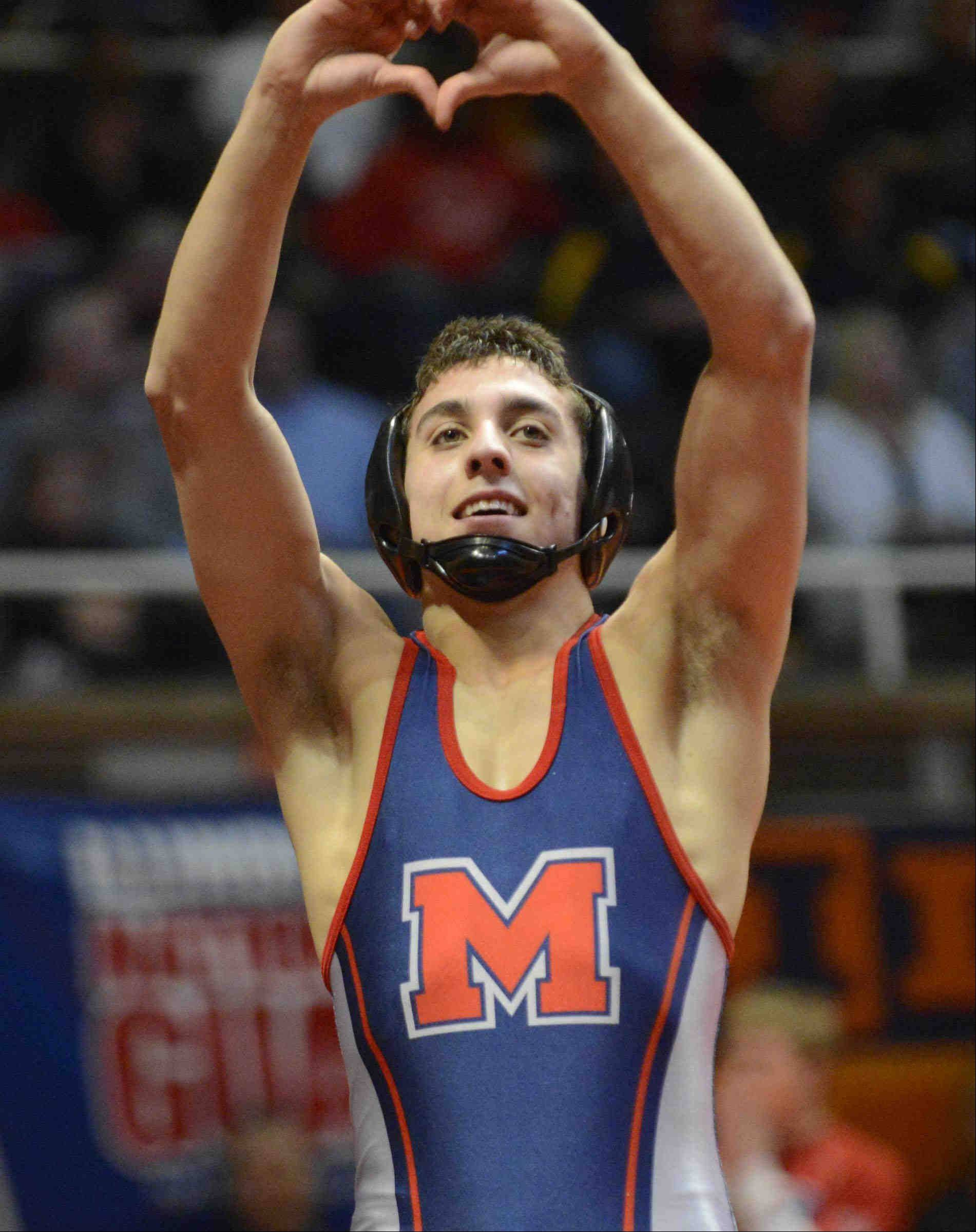 Marmion Academy's Johnny Jimenez signals the crowd after defeating Sebastian Pique of Sandburg in the Class 3A 120-pound IHSA championship final wrestling match at Assembly Hall in Champaign.