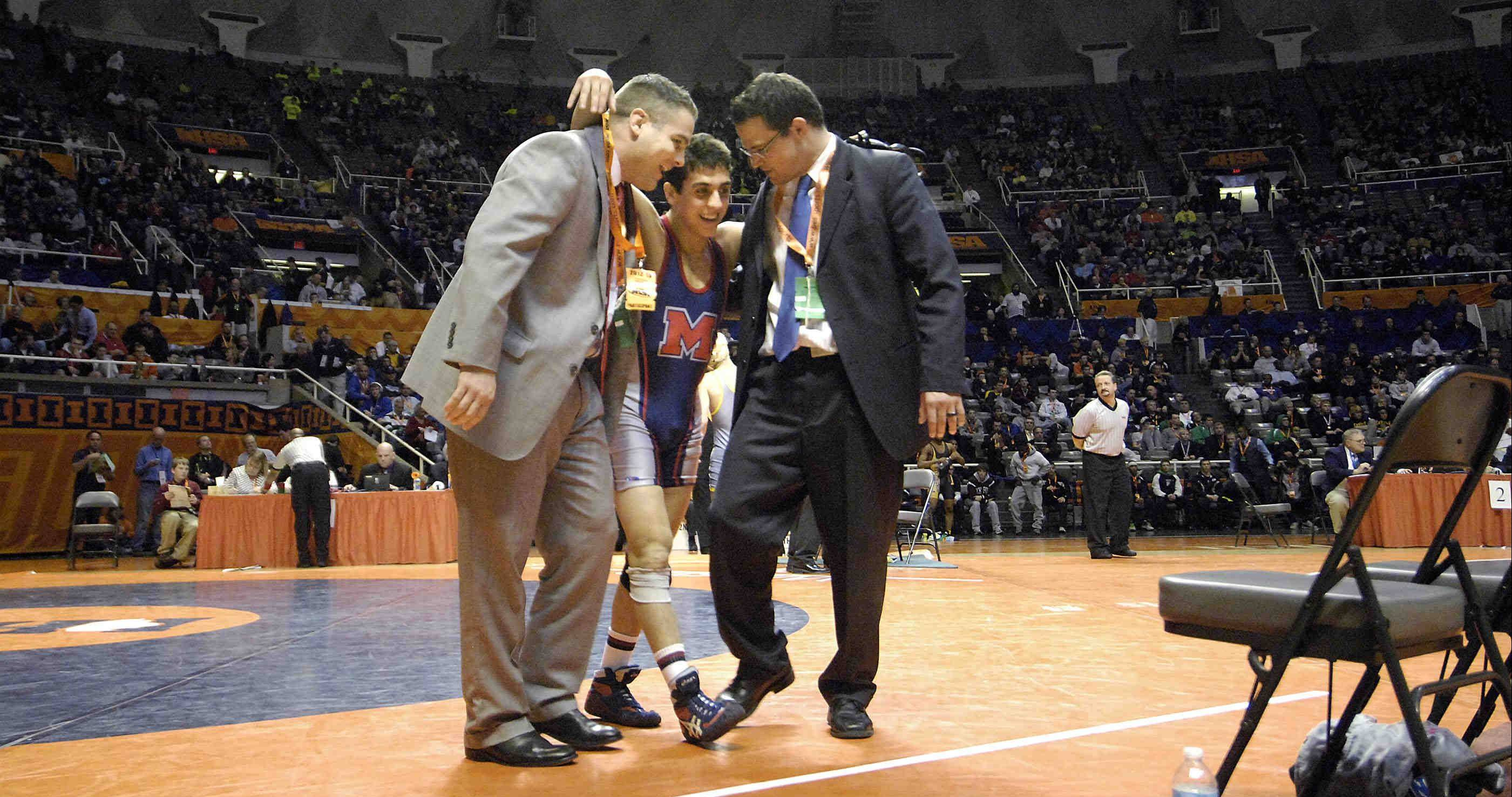 Johnny Jimenez is flanked by his Marmion Academy coaches after winning the Class 3A 120-pound IHSA championship final wrestling match at Assembly Hall in Champaign Saturday.