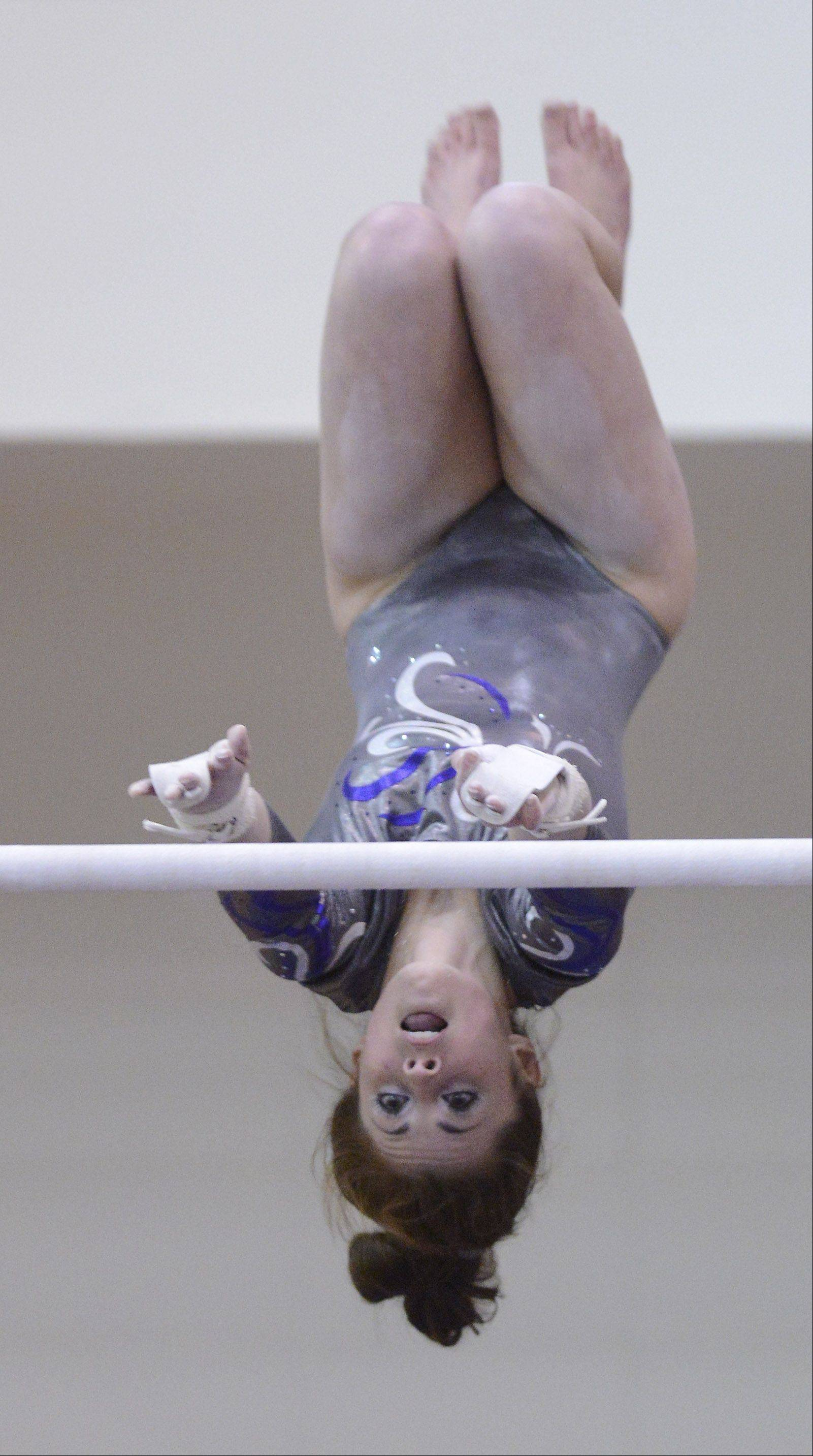 Abby Madden of St. Edward competes on the uneven parallel bars during the girls gymnastics state finals at Palatine High School on Saturday.