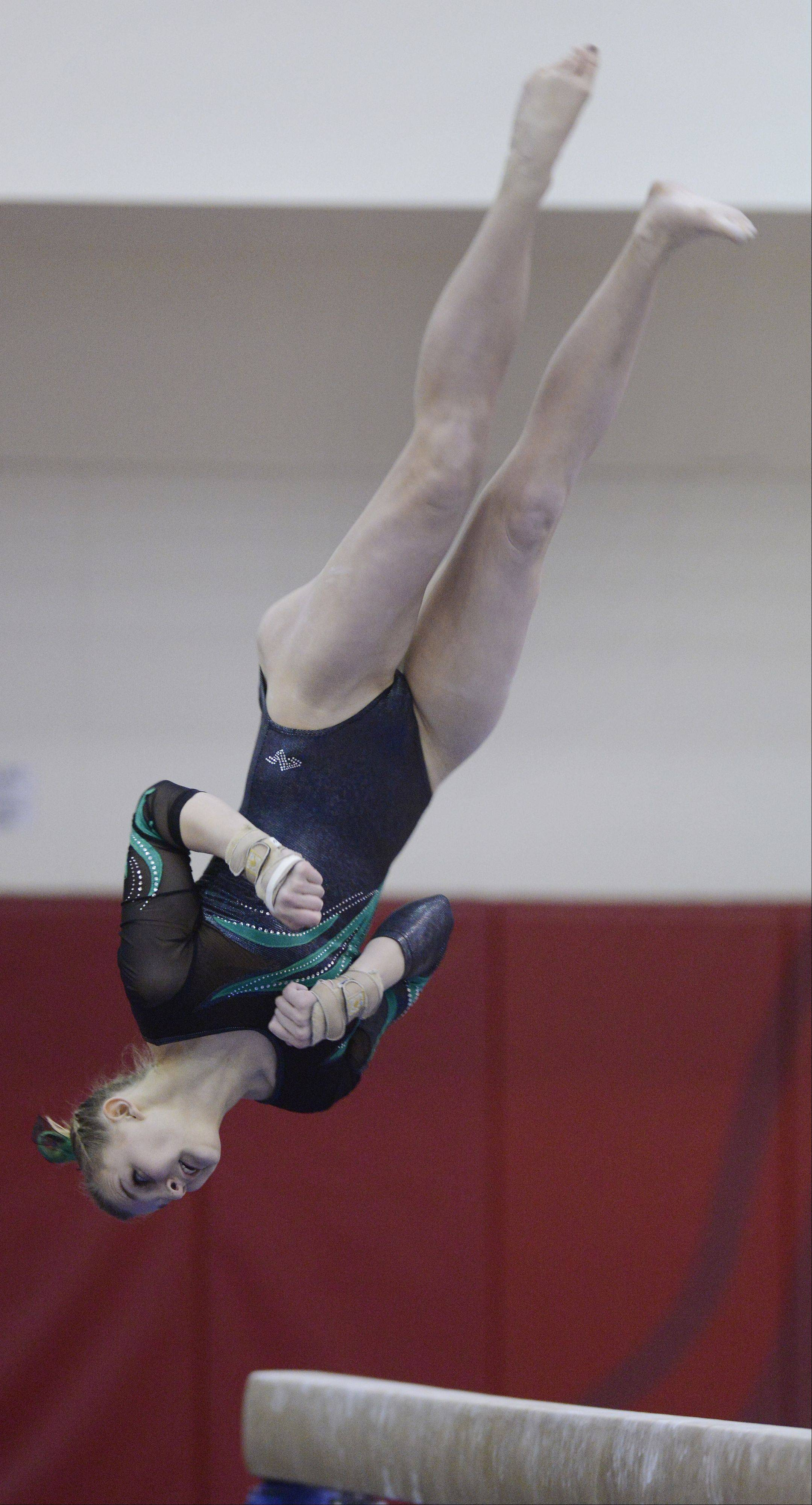 Fremd's Sydney Plichta dismounts from the balance beam during the girls gymnastics state finals at Palatine High School on Saturday.