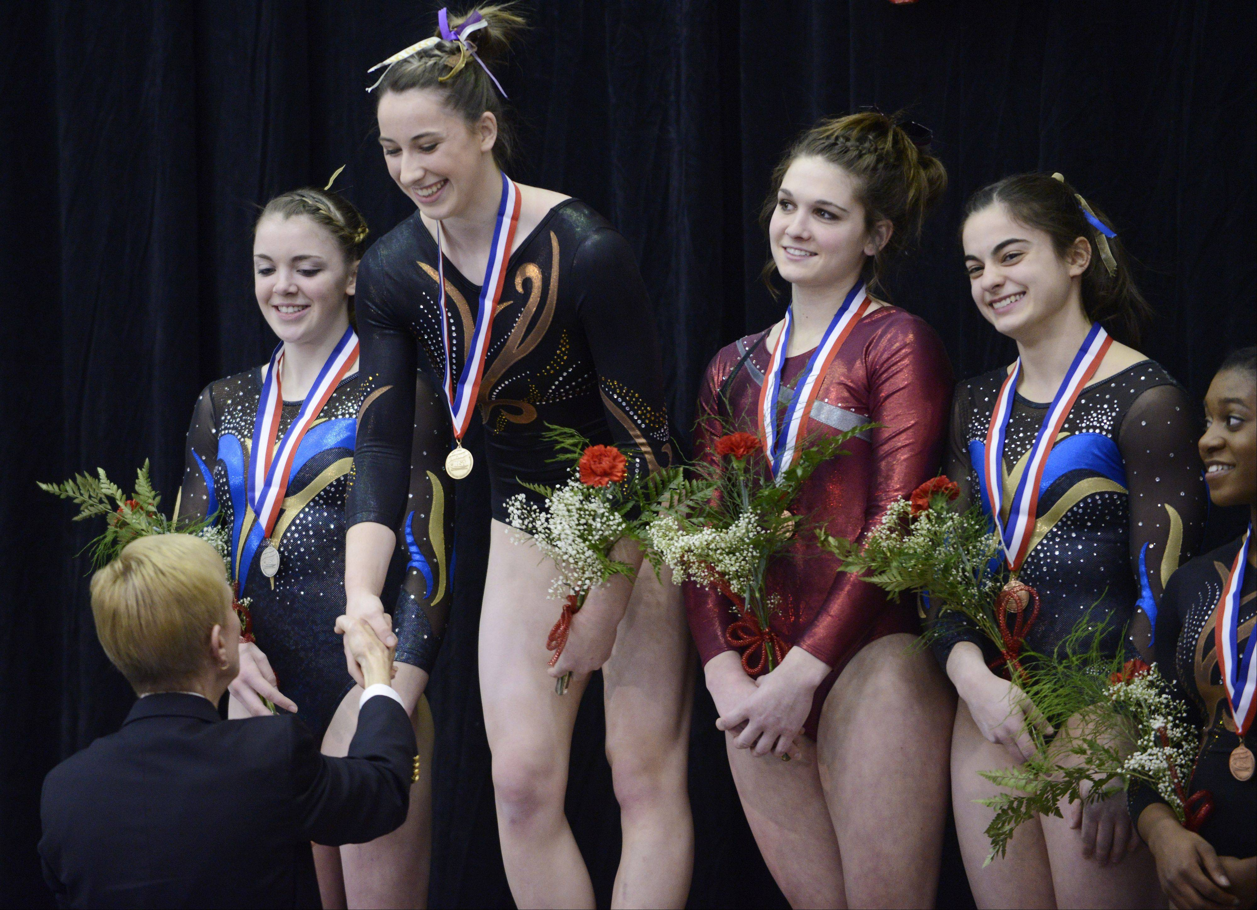Lauren Feely of Carmel, second from left, receives her medal following the vault during the girls gymnastics state finals at Palatine High School on Saturday.