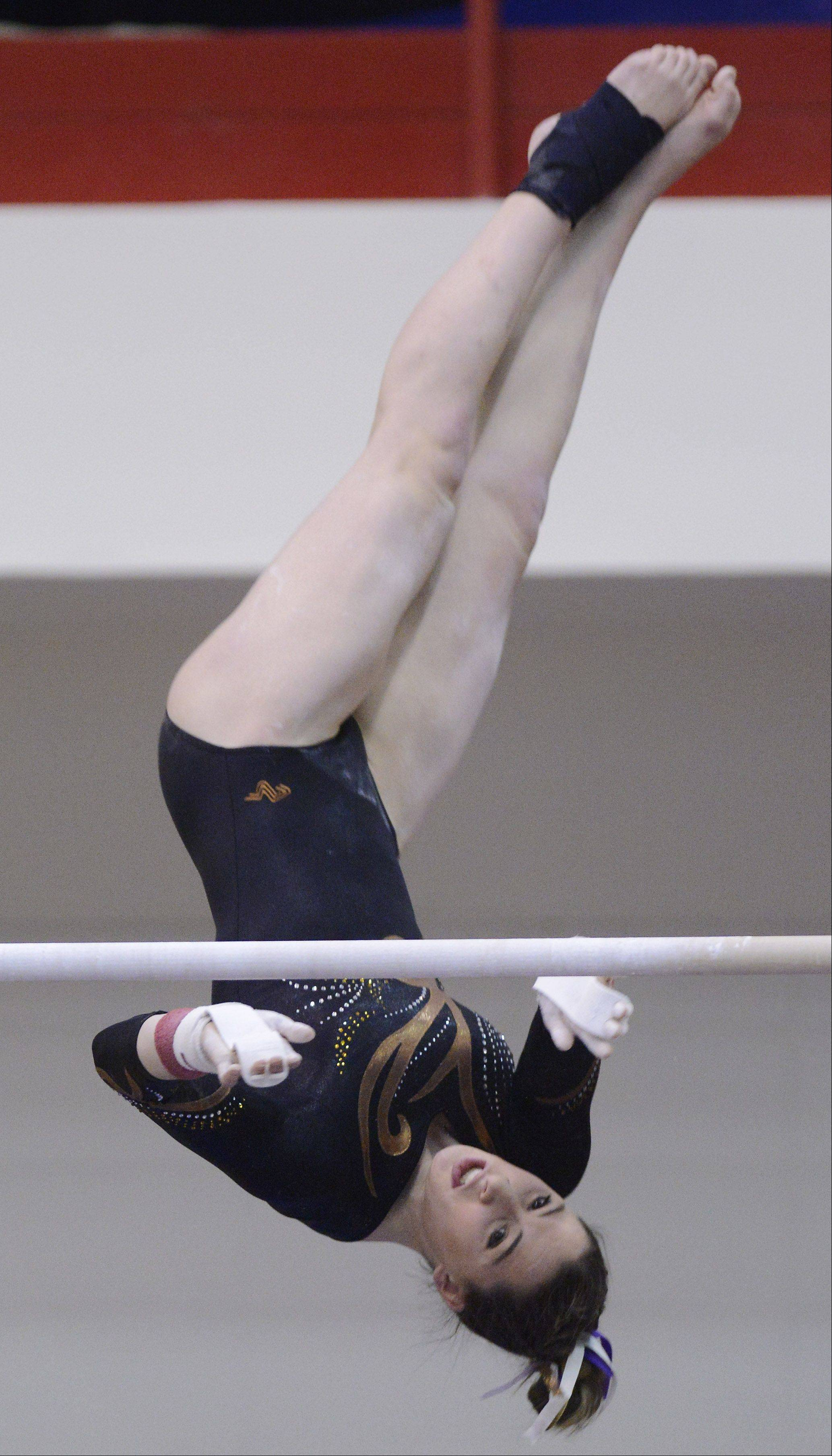 Lauren Feely of Carmel competes on the uneven parallel bars during the girls state gymnastics finals at Palatine High School Saturday.