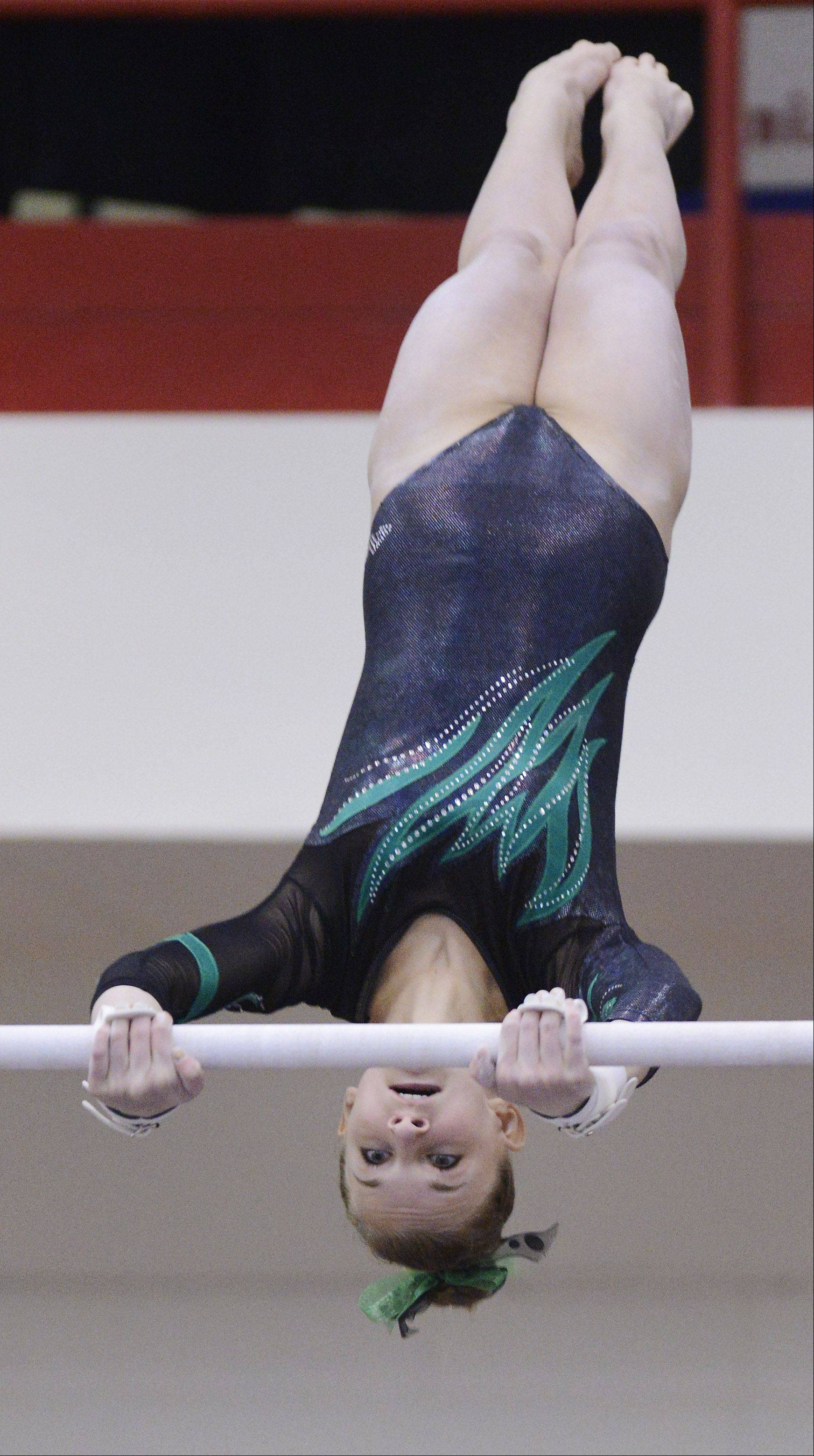 Sydney Plichta of Fremd competes on the uneven parallel bars during the girls state gymnastics finals at Palatine High School Saturday.