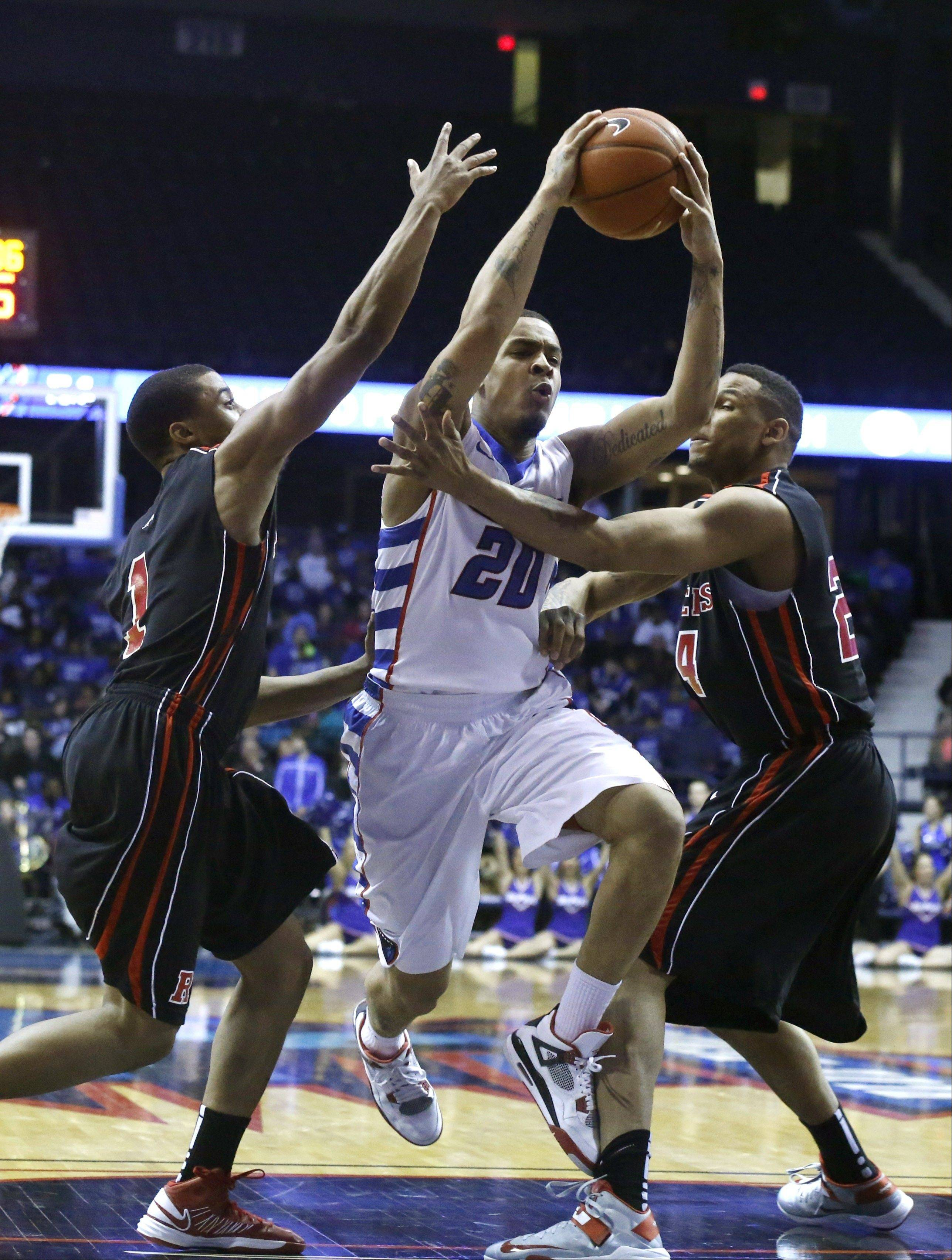 DePaul guard Brandon Young, center, splits the Rutgers defense of Jerome Seagears (1) and Vincent Garrett (24) during the second half Saturday.