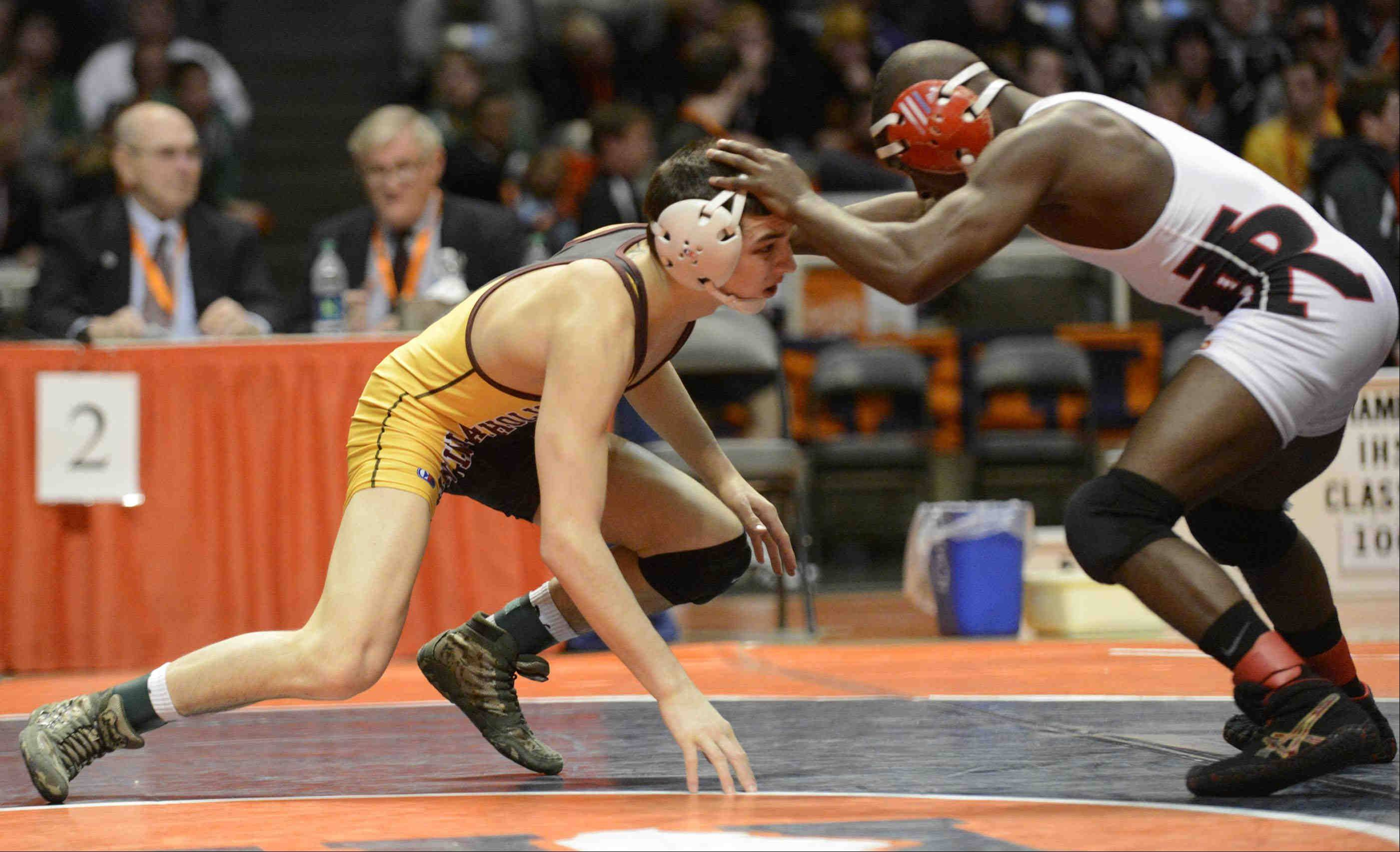 Lombard Montini's Vince Turk is held off by BJ McGhee of Rock Island in the Class 2A 120-pound IHSA championship final wrestling match at Assembly Hall in Champaign. Turk lost the match.