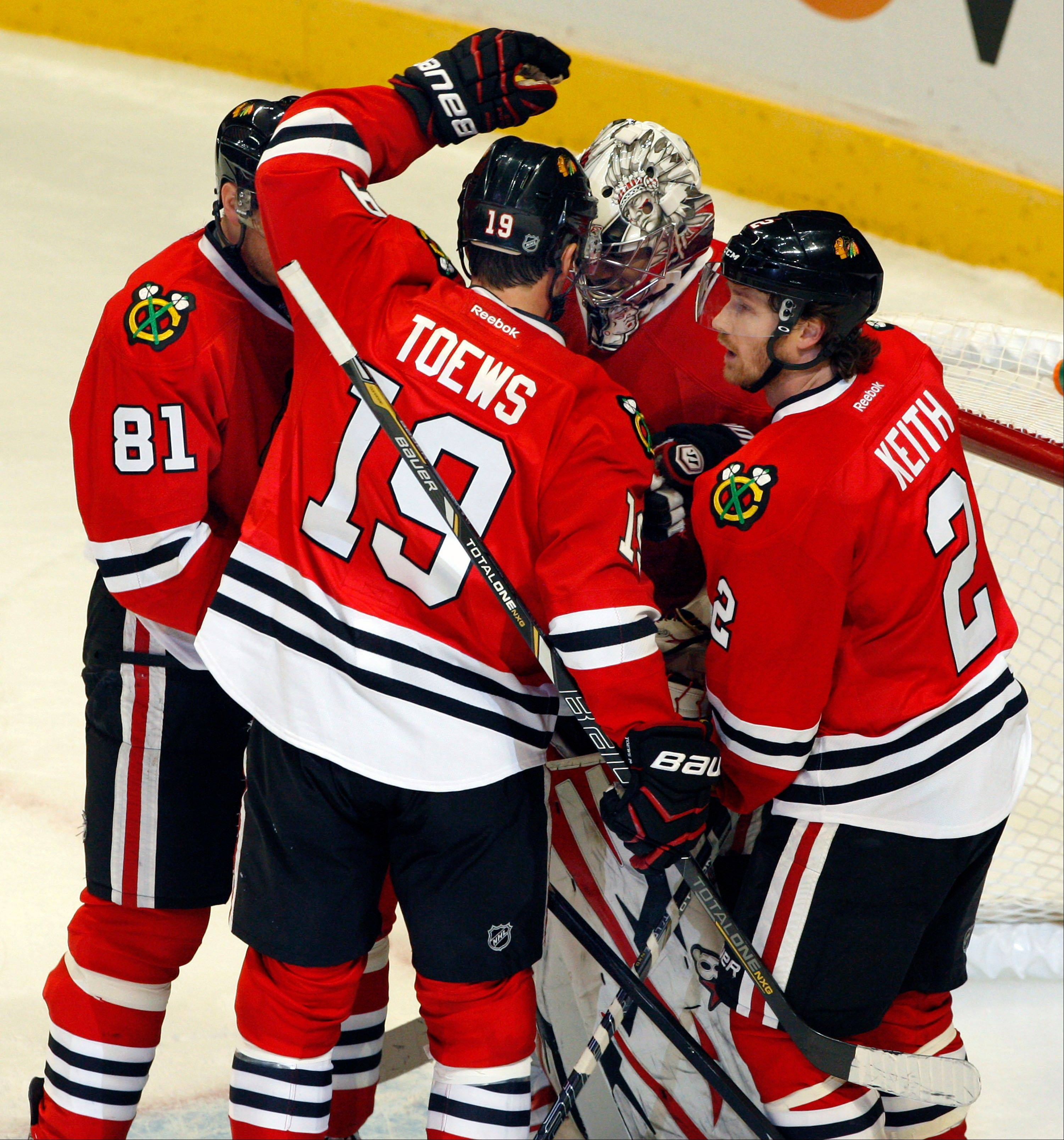 Marian Hossa (81), Jonathan Toews (19) and Duncan Keith (2) congratulate goalie Ray Emery after the Blackhawks� 3-2 victory Sunday over the Kings.