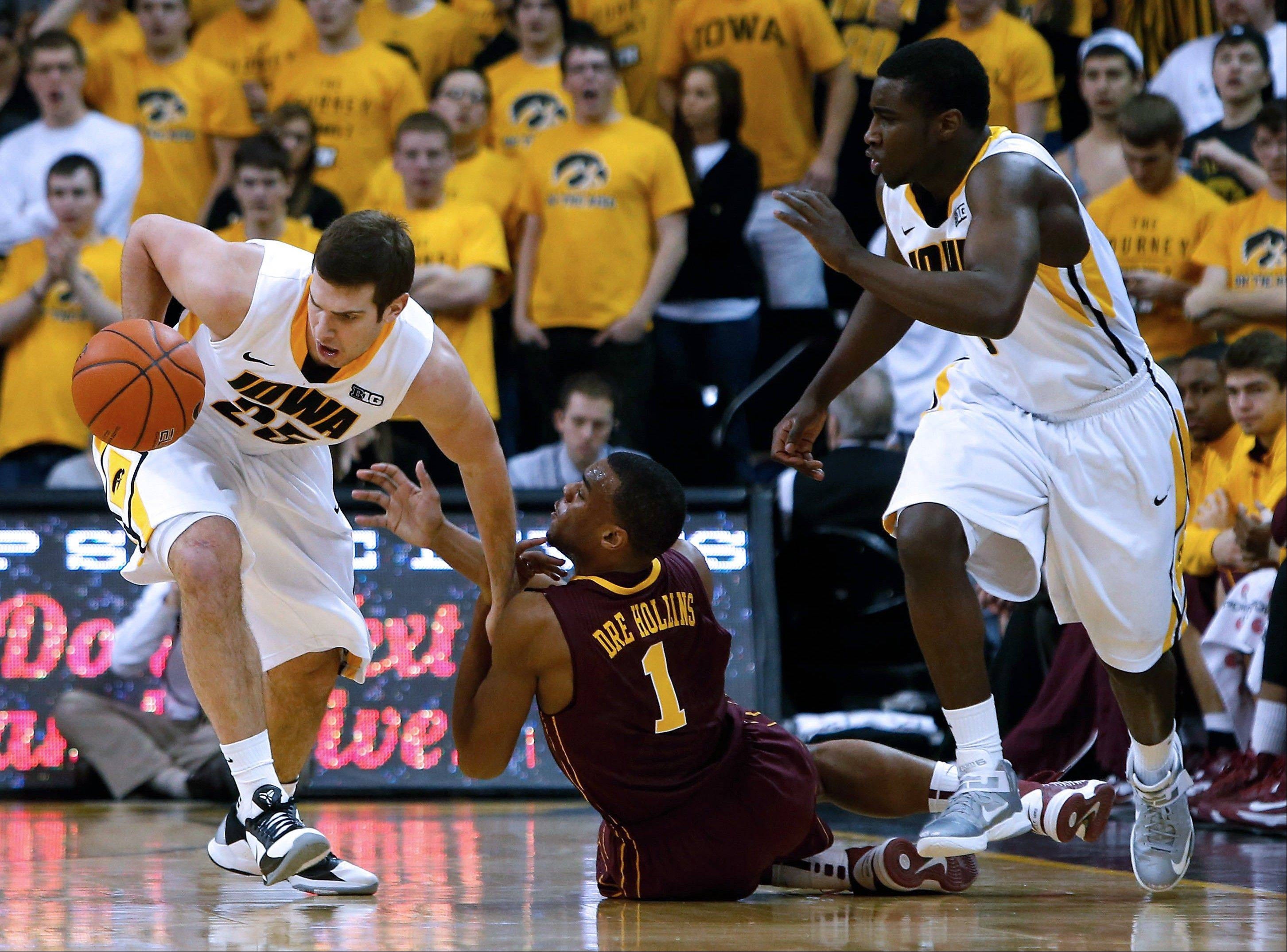 Iowa guard/forward Eric May (25) draws a foul as he steals the ball from Minnesota guard Andre Hollins (1) during the second half Sunday in Iowa City, Iowa.