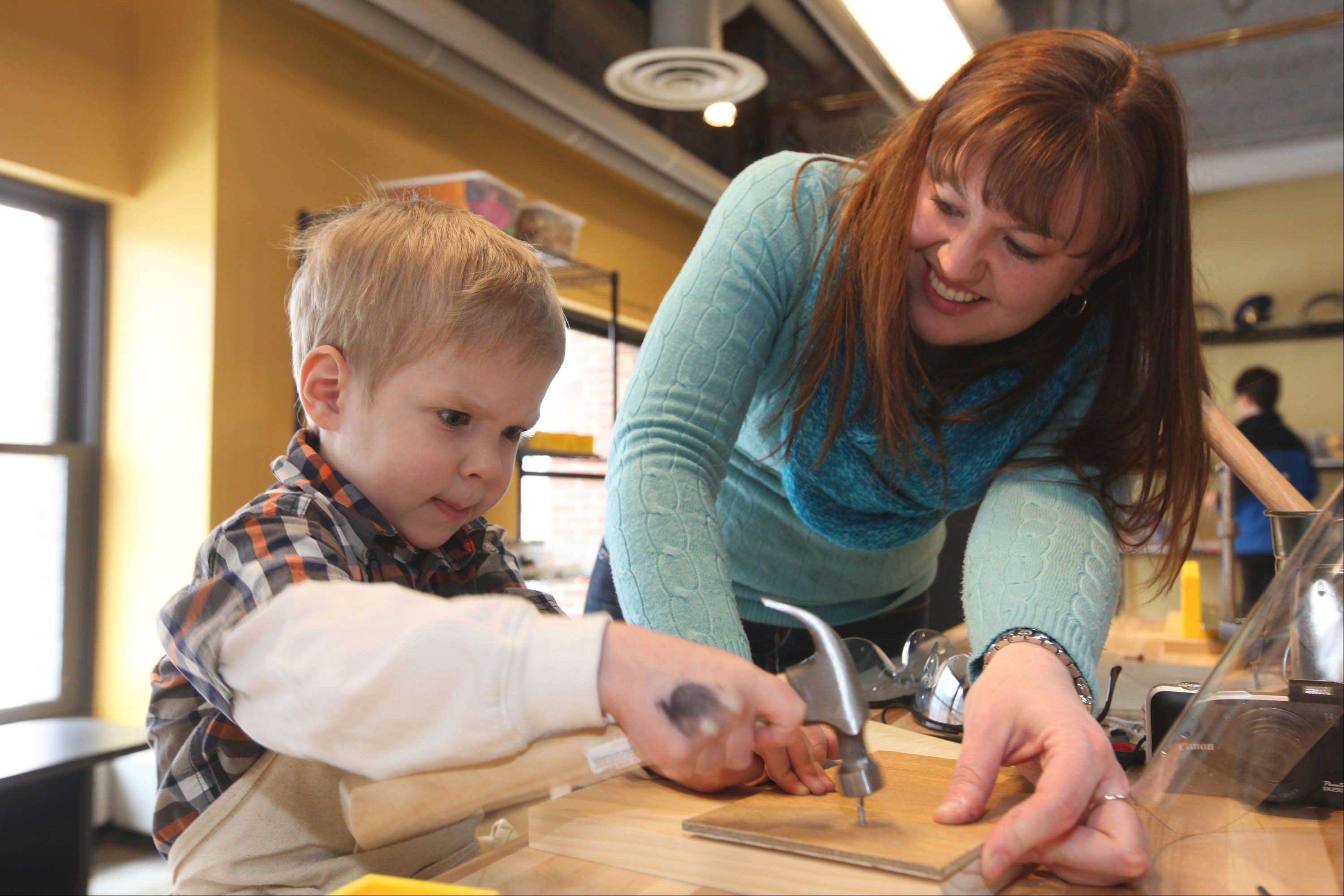 With the help of an adult, children get a chance to try out tools in the Tinkering Lab at the Chicago Children's Museum.