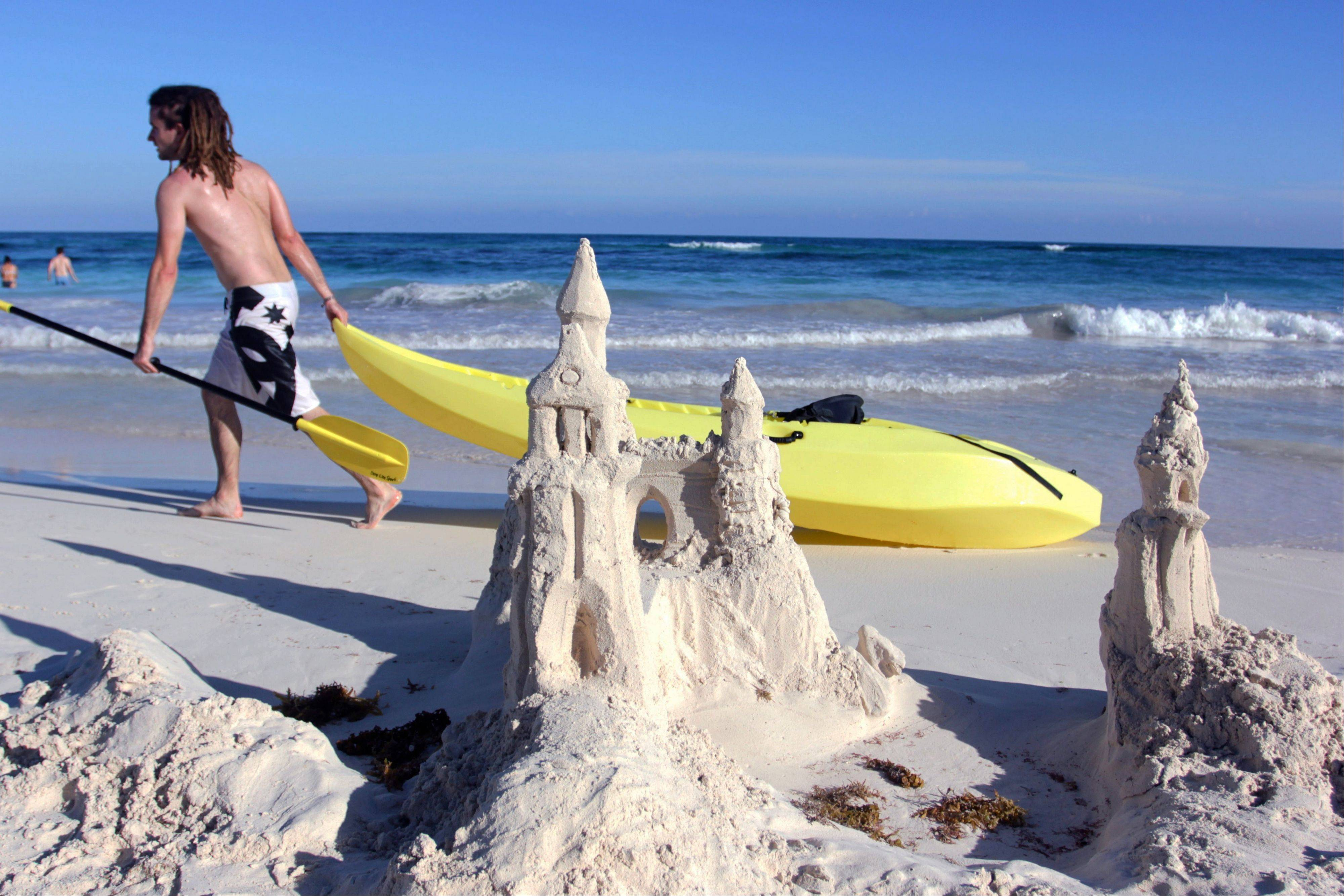 A man drags a kayak past a sand castle in Tulum, Mexico.