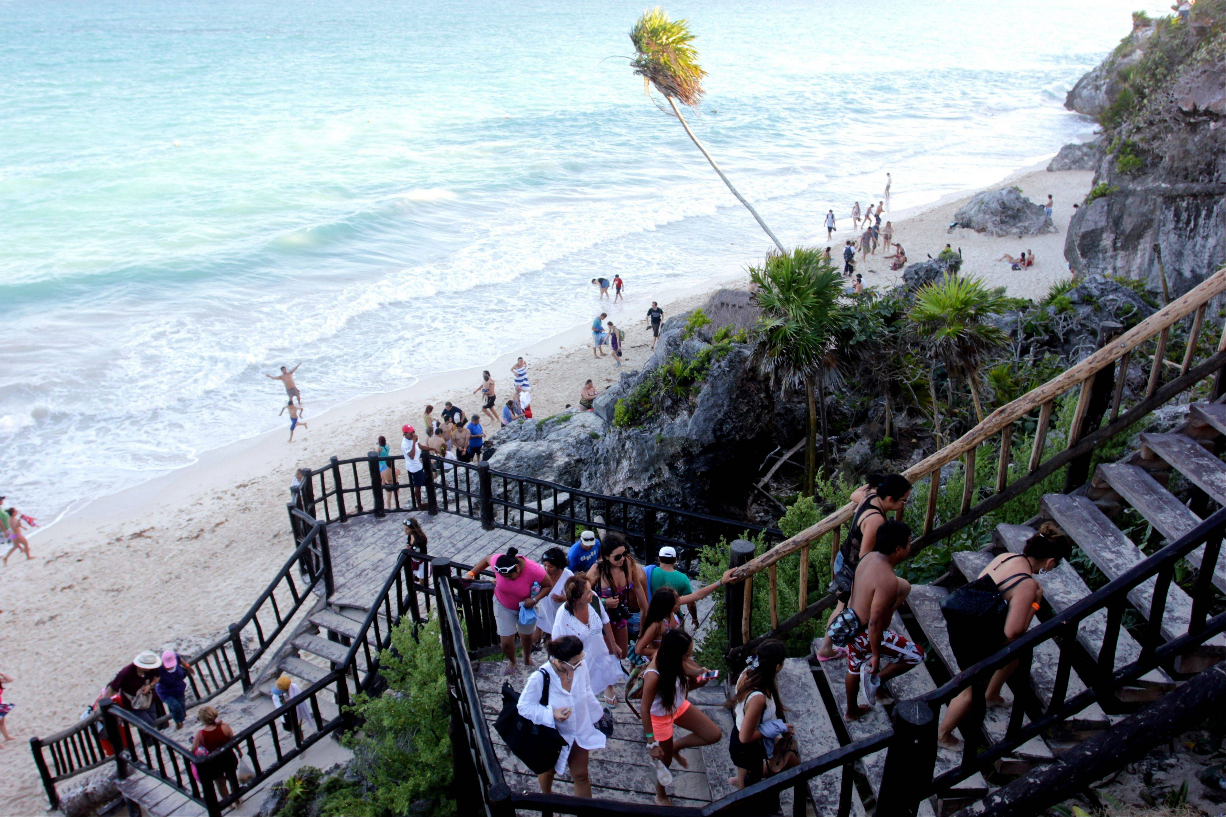 A line of people leave the swimming beach next to the Mayan ruins in Tulum.