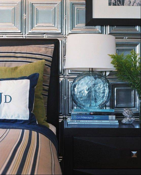 A master bedroom designed by Kyle Schuneman of Live Well Designs shows a bedside table lamp reminiscent of a melting chunk of ice and a wall lined with shimmery, metal ceiling tiles bringing some frosty winter style to a southern California home.