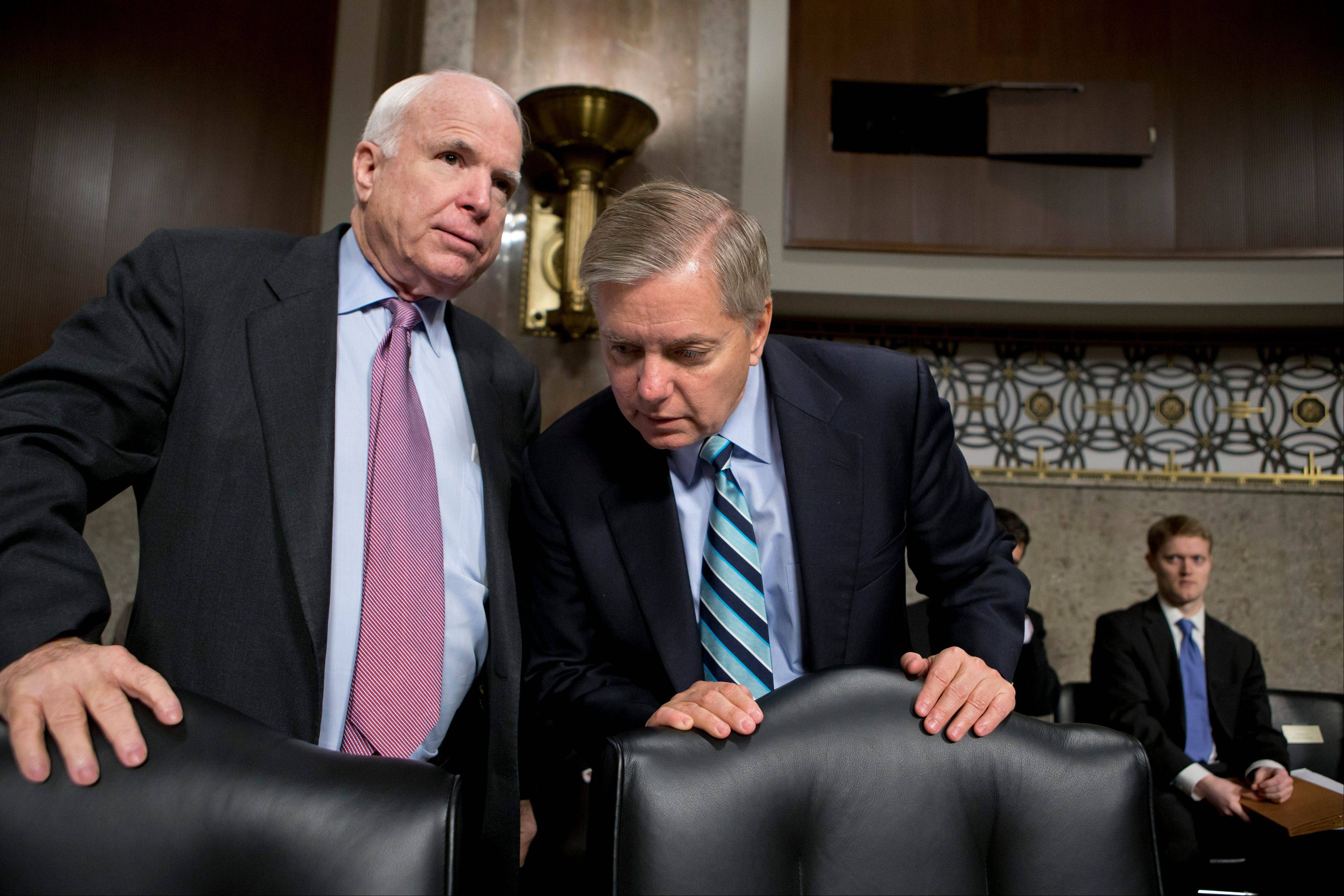 Republican Sens. John McCain, left, and Lindsey Graham confer at the start of a Senate Armed Services Committee hearing on the appointment Chuck Hagel to be the next Secretary of Defense on Feb. 14.