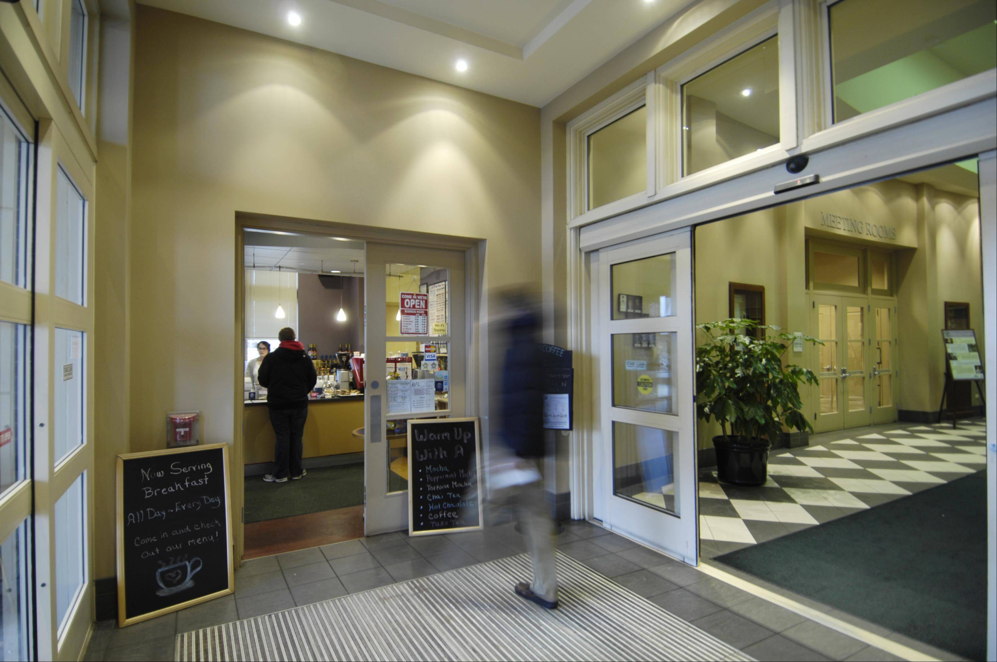 A patron walks with a library book to the 10 South Cafe in the Batavia Public Library lobby.