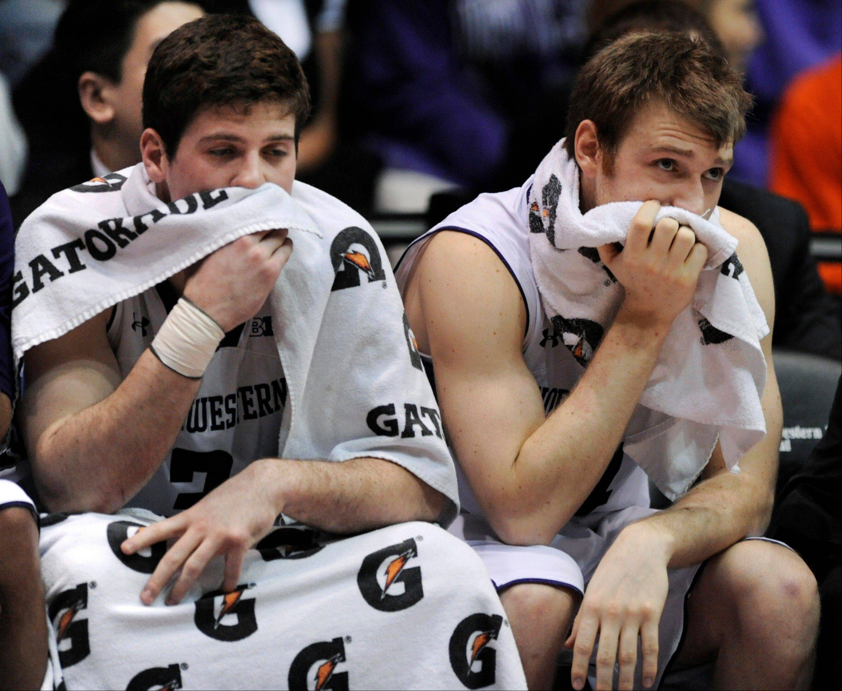 Northwestern's Dave Sobolewski left, and Alex Marcotullio sit on the bench during the second half against Illinois, Sunday. Illinois won 62-41.