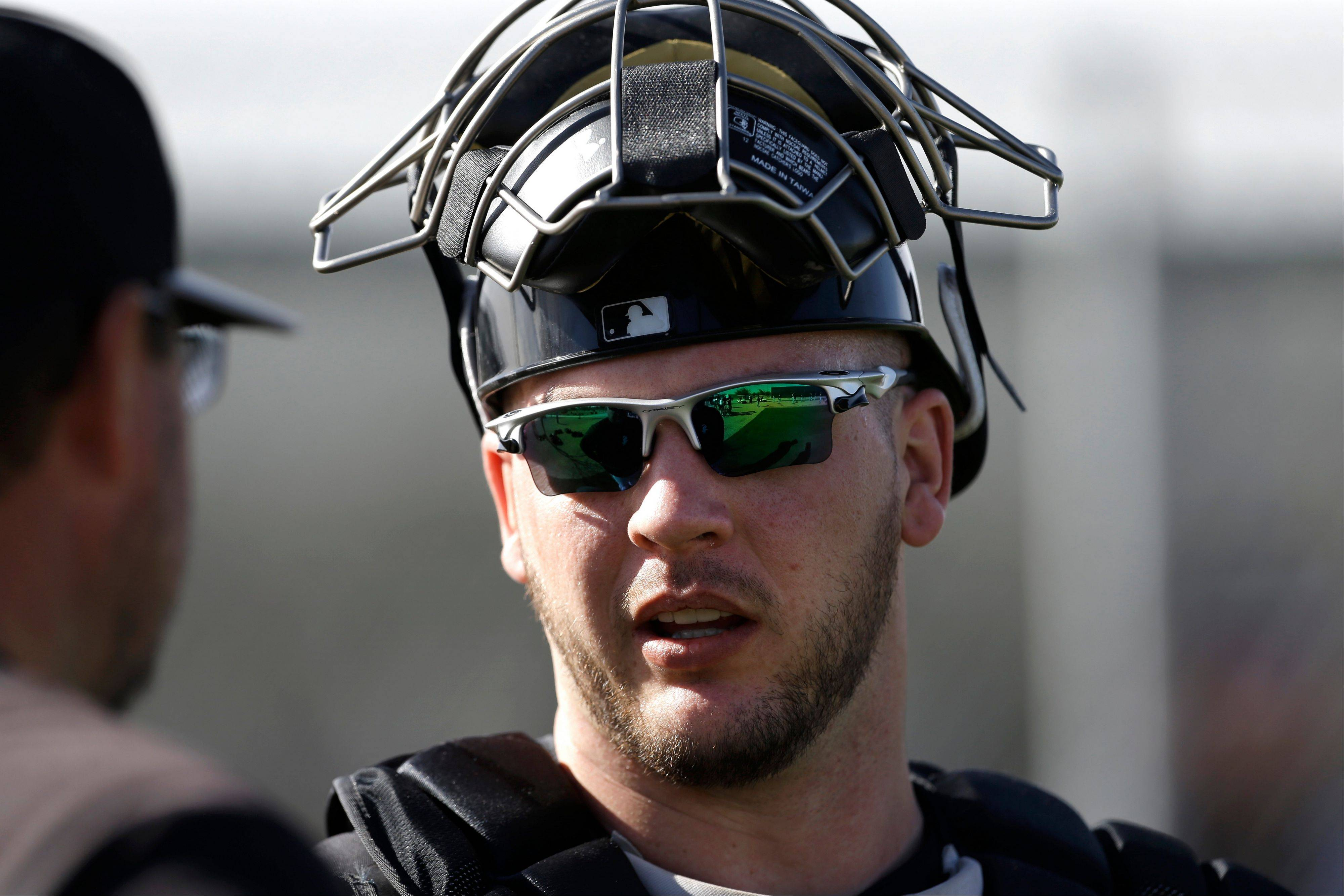 Chicago White Sox catcher Tyler Flowers talks to a coach during spring training baseball in Phoenix on Friday.