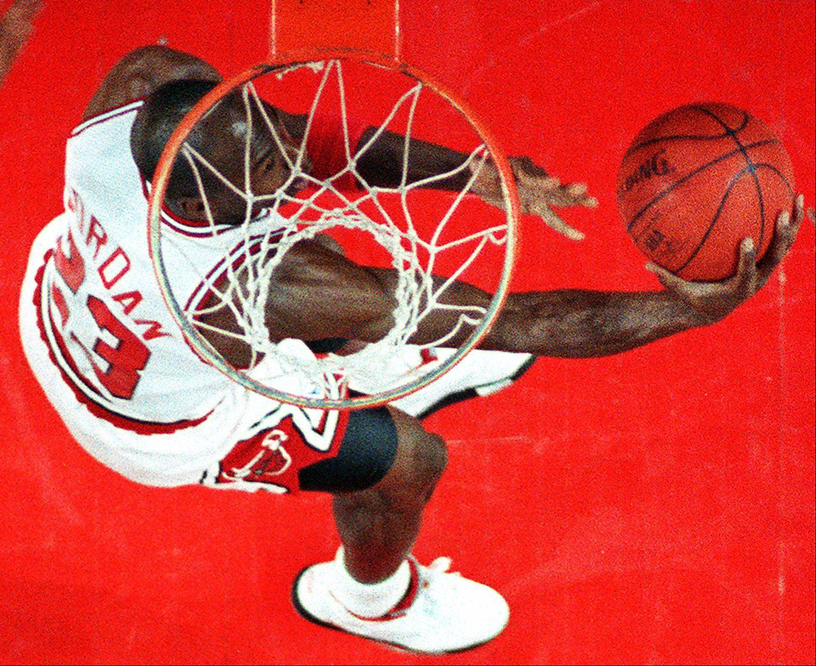 Michael Jordan under the basket prepares for a slam in the paint during a regular season game at the Chicago Stadium.