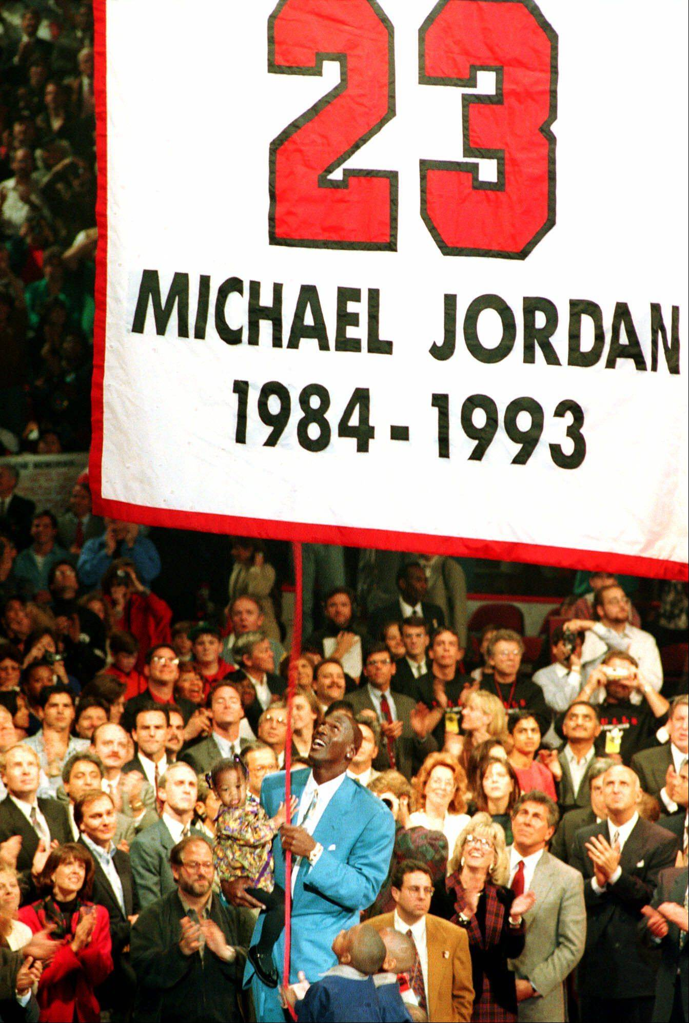 Former Chicago Bulls forward Michael Jordan holds his daughter, Jasmine, as his sons, Jeffrey, left center, and Marcus help him hoist a banner up to the rafters of the United Center Nov.1,1994 in Chicago. Banner carries Jordan's number 23, which was retired during the ceremony. A 12-foot bronze statue was also unveiled outside the stadium to honor Jordan.