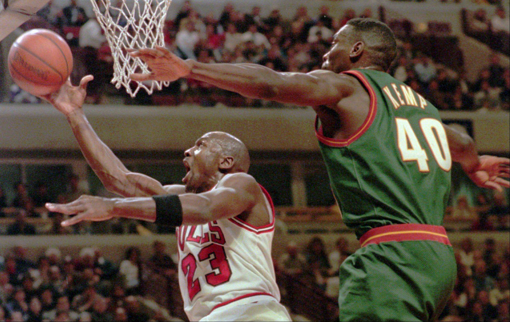 Michael Jordan (23) takes a shot in front Seattle SuperSonics' Shawn Kemp (40) during the first quarter Wednesday, Jan. 10, 1996, in Chicago.