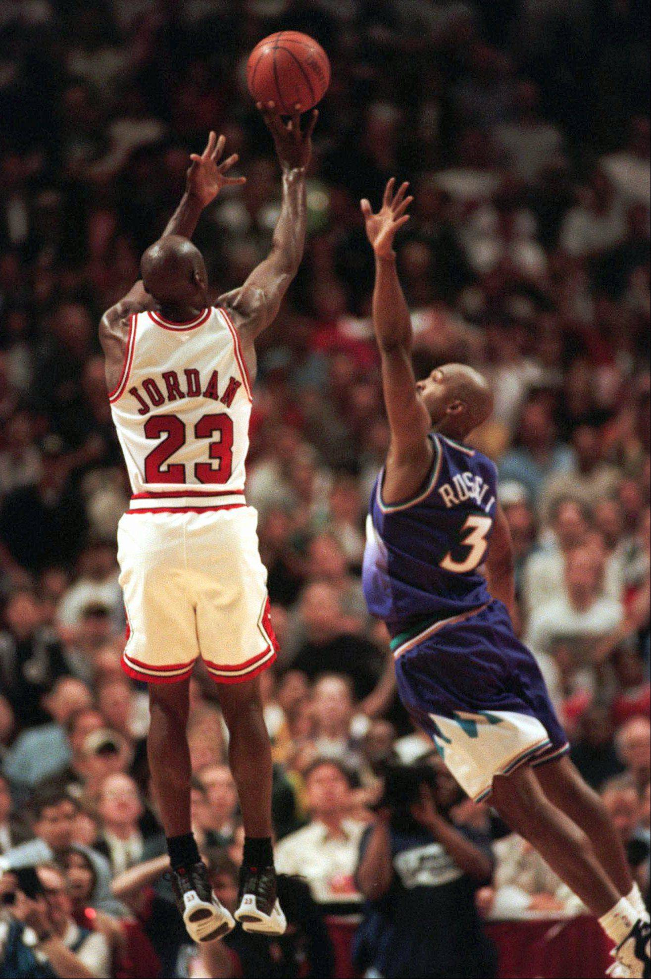 Michael Jordan puts up the game-winning shot over Utah Jazz forward Bryon Russell, right, to win Game 1 of the NBA Finals 84-82 Sunday, June 1, 1997, in Chicago.