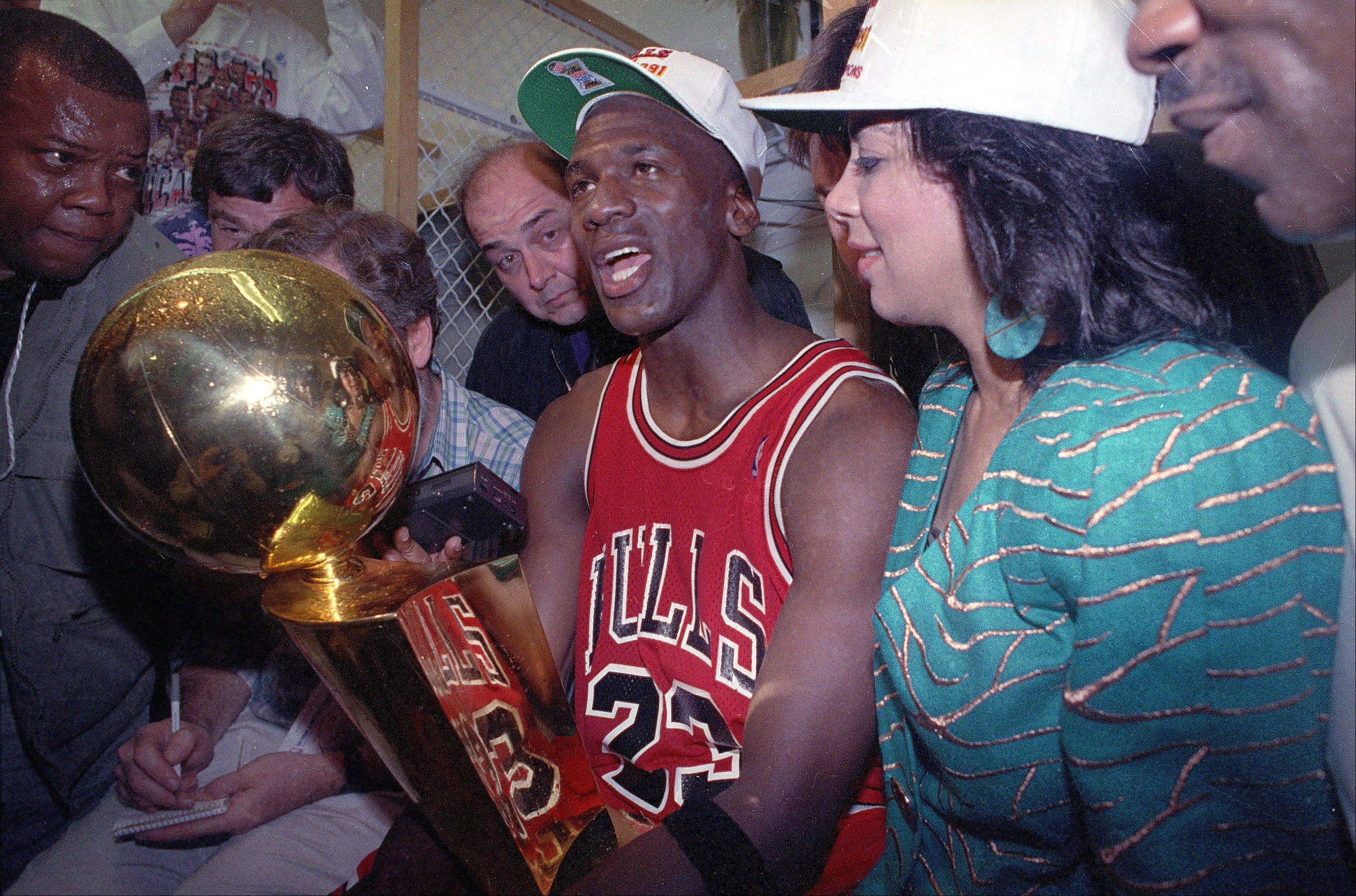 Chicago Bulls' Michael Jordan holds the trophy after the Bulls won over the Los Angeles Lakers, 108-101, in game five of the NBA championship in Inglewood, Calif., June 12, 1991.