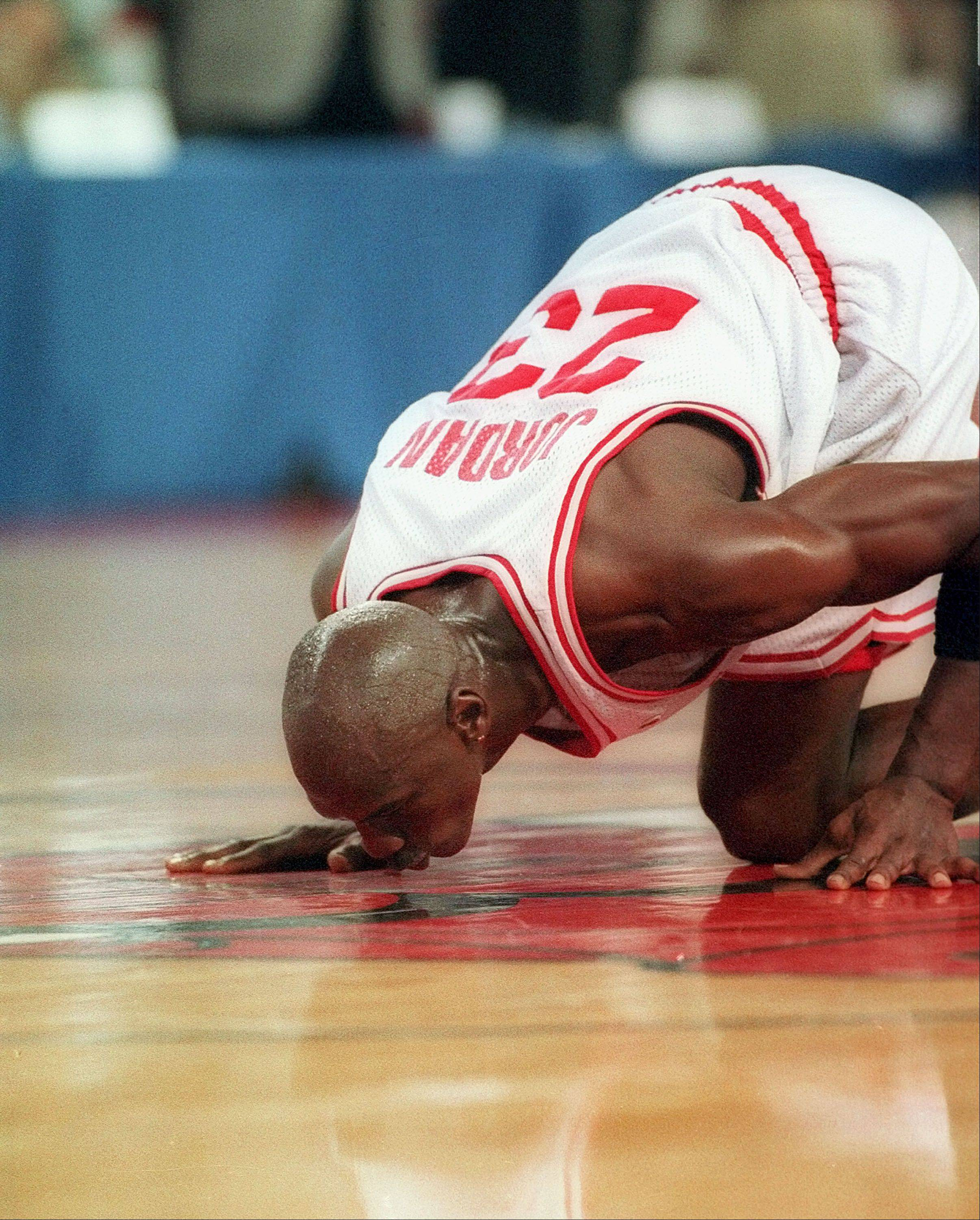 Michael Jordan kisses the basketball floor of the Chicago Stadium as he leaves it for the last time after a charity basketball game in Chicago, Ill., on Friday, Sept., 9, 1994. Jordan played his first three championships seasons at Chicago stadium before a stint playing minor league baseball with the Birmingham Barons. Chicago Stadium was to be replaced by the new United Center across the street.
