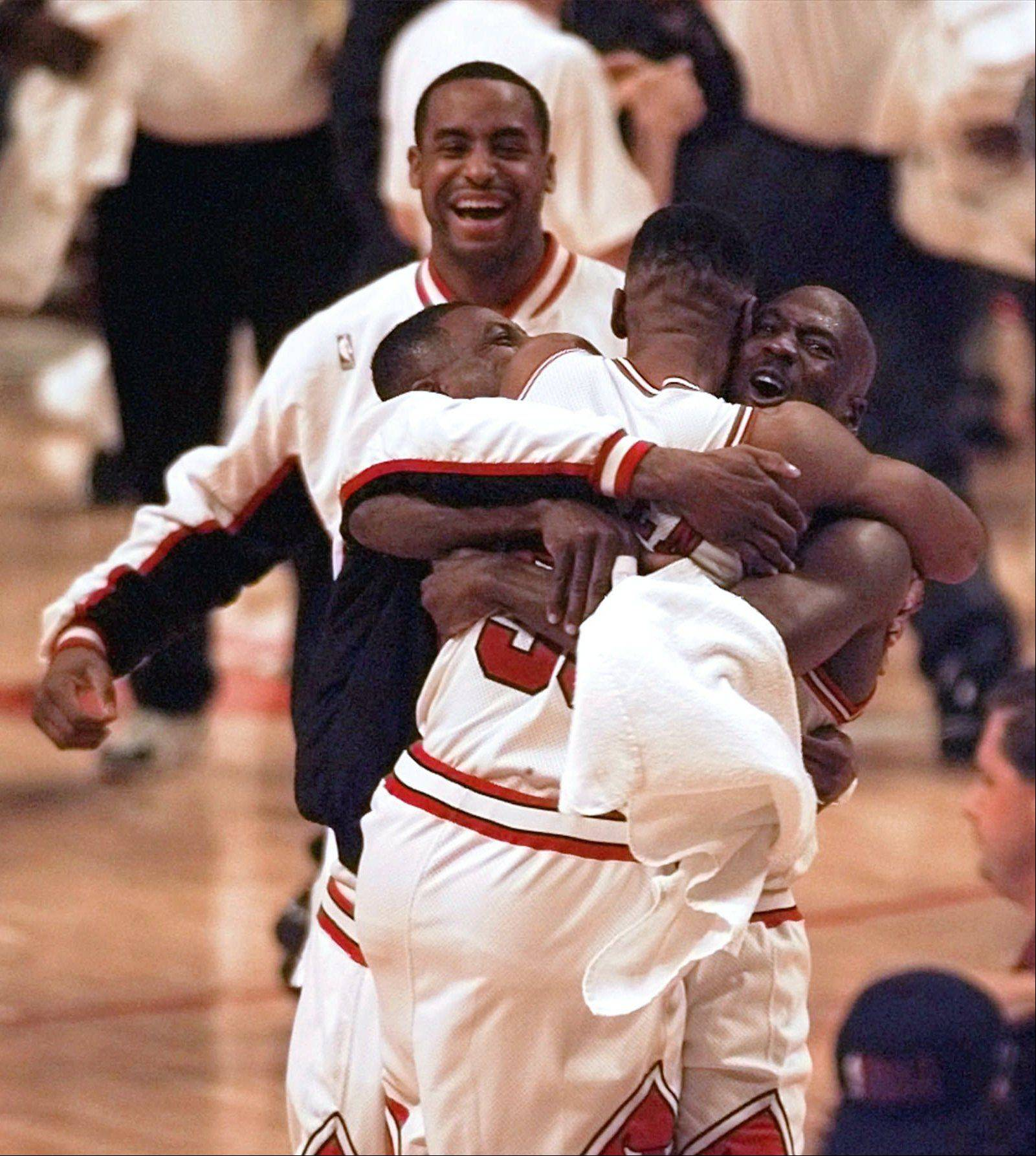Michael Jordan hugs teammates Scottie Pippen, front, and Randy Brown, left, as Jason Caffey, rear, joins in after the Bulls beat the Utah Jazz 90-86 in Game 6 to win the NBA championship Friday, June 13, 1997, in Chicago.