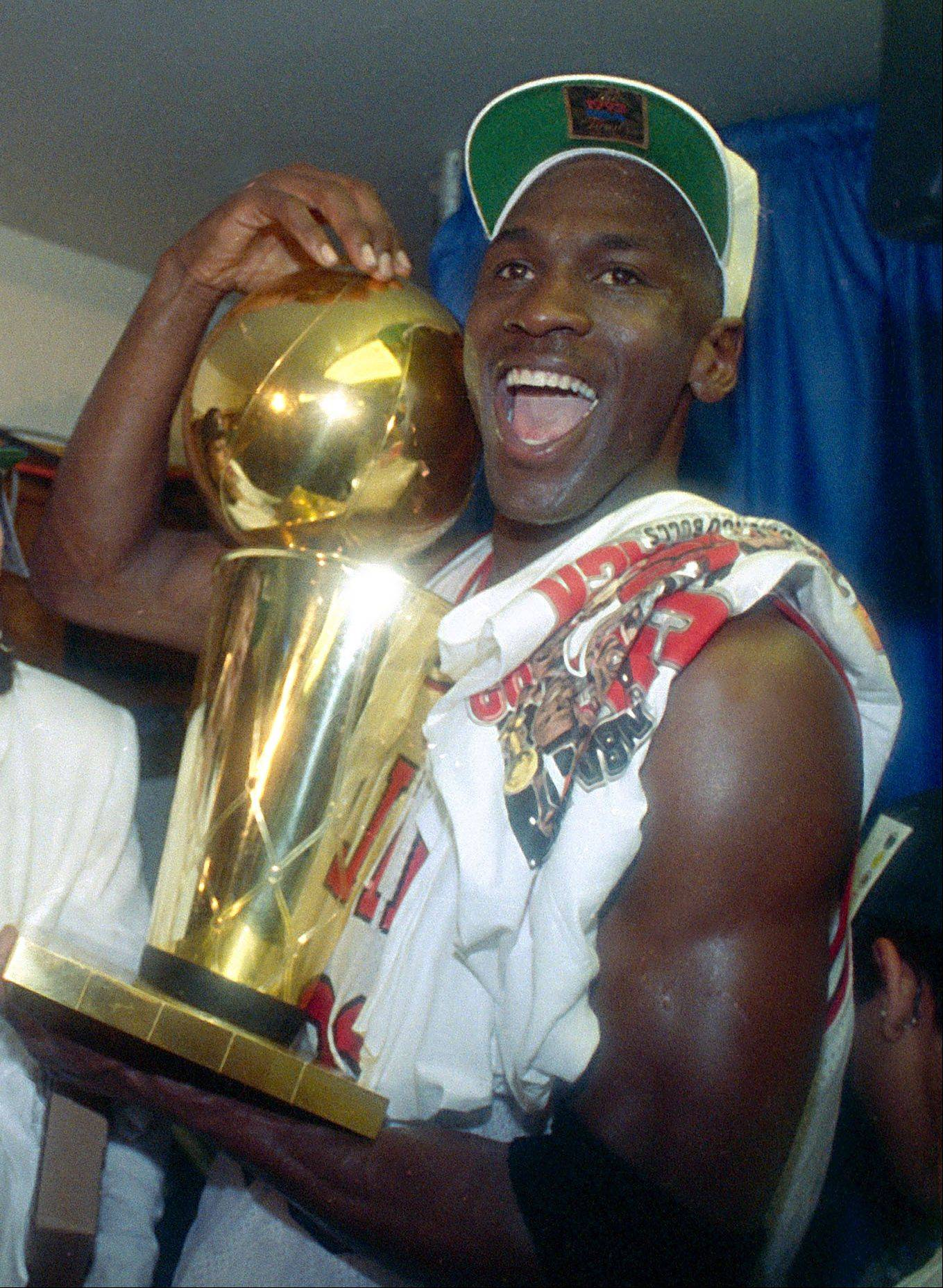 This is a june 14, 1992 file photo showing Chicago Bulls' Michael Jordan celebrating with the NBA trophy after the Bulls beat the Portland Trail Blazers 97-93 in Chicago, to win their second straight NBA title.